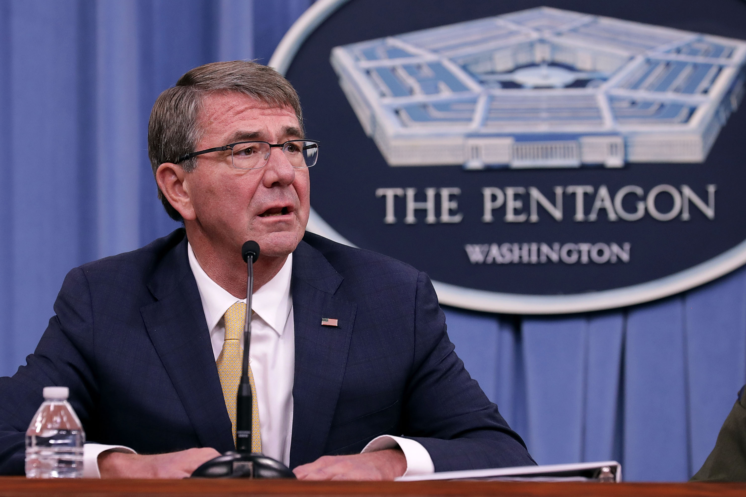 """Former Defense Secretary Ash Carter seated in front of a sign with a picture of the Pentagon building and the words """"The Pentagon, Washington."""""""