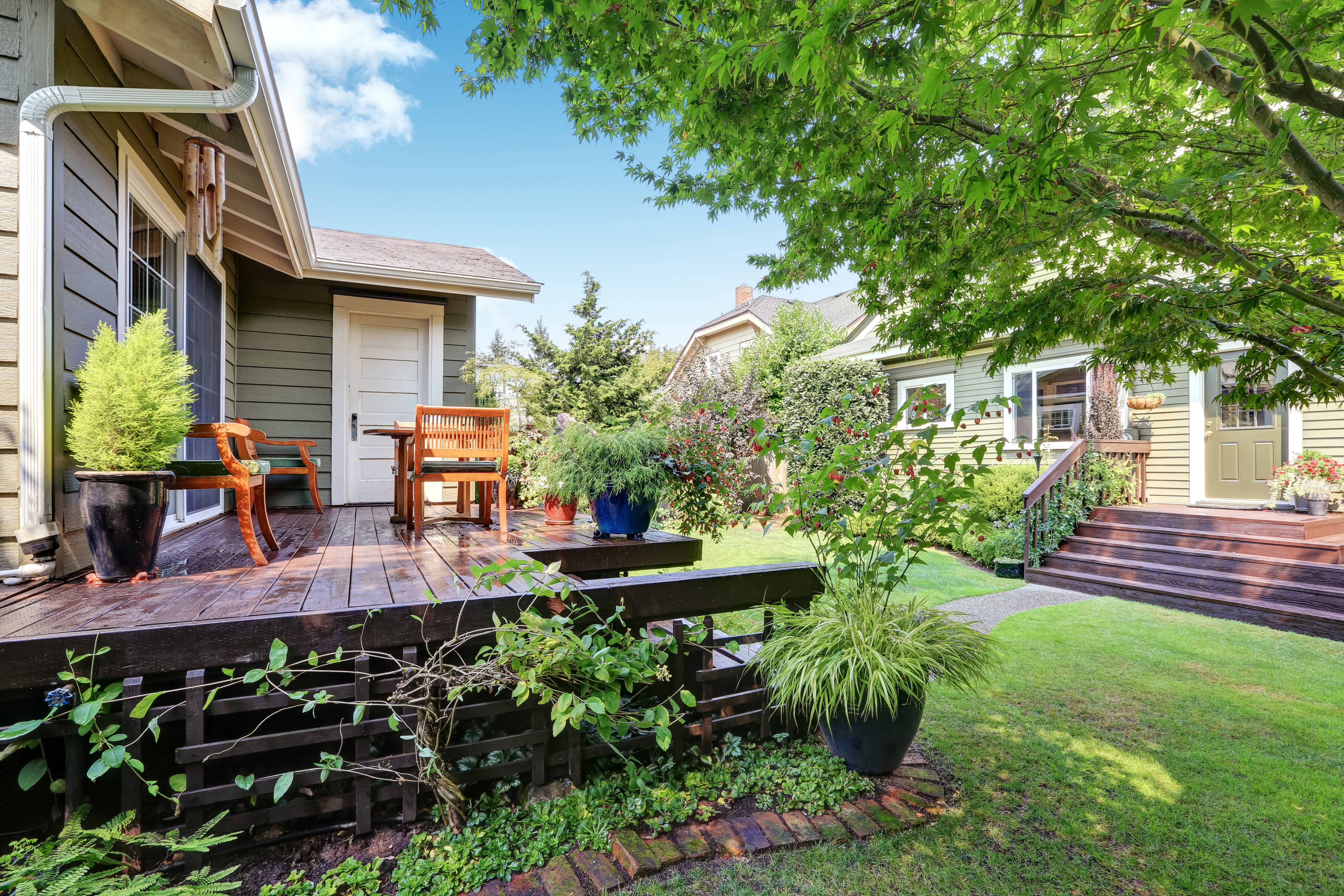 Two homes are separated by a backyard lawn.
