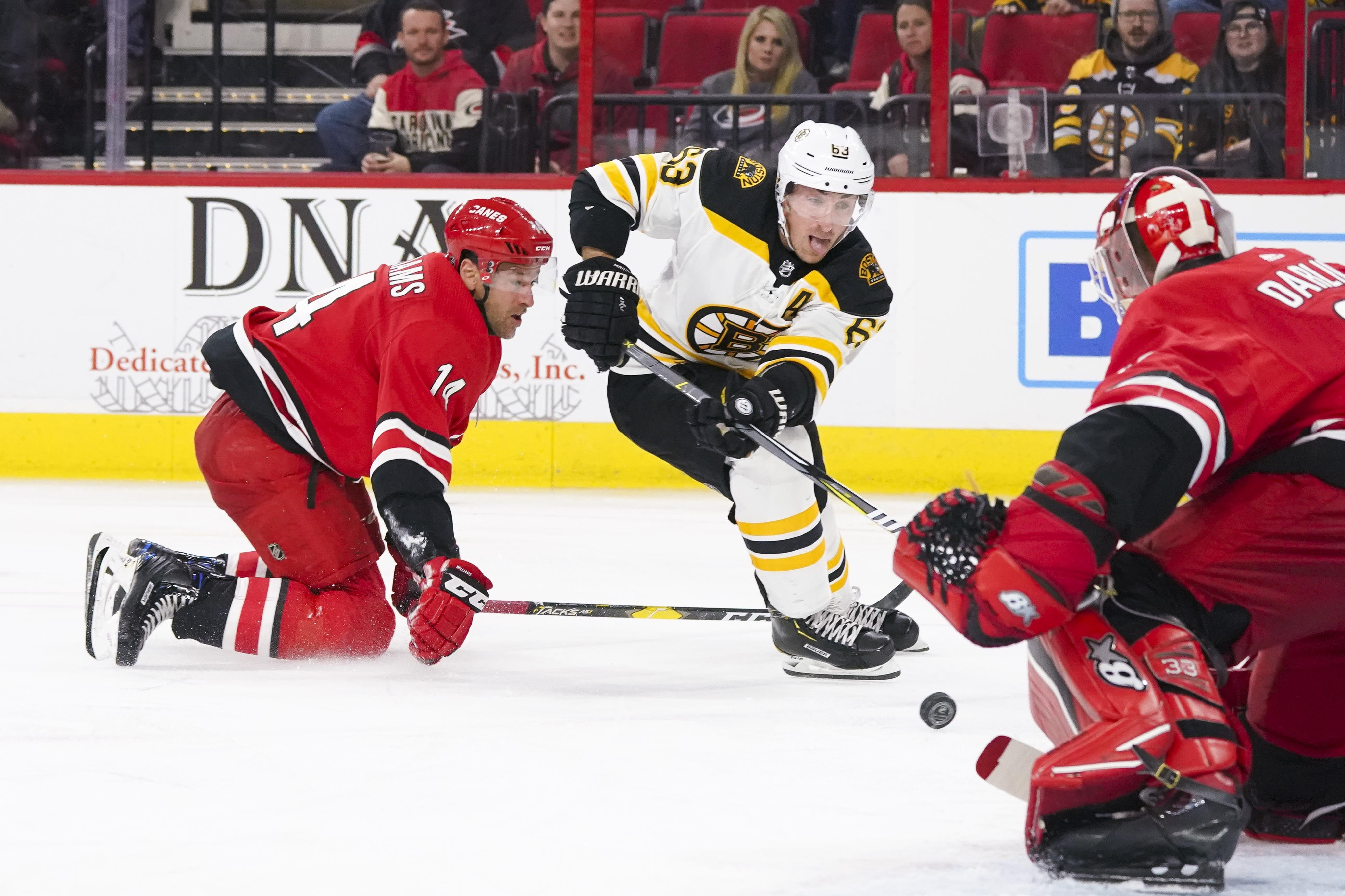 Oct 30, 2018; Raleigh, NC, USA; Boston Bruins left wing Brad Marchand (63) skates with the puck past Carolina Hurricanes right wing Justin Williams (14) during the third period at PNC Arena. The Boston Bruins defeated the Carolina Hurricanes 3-2. Mandator