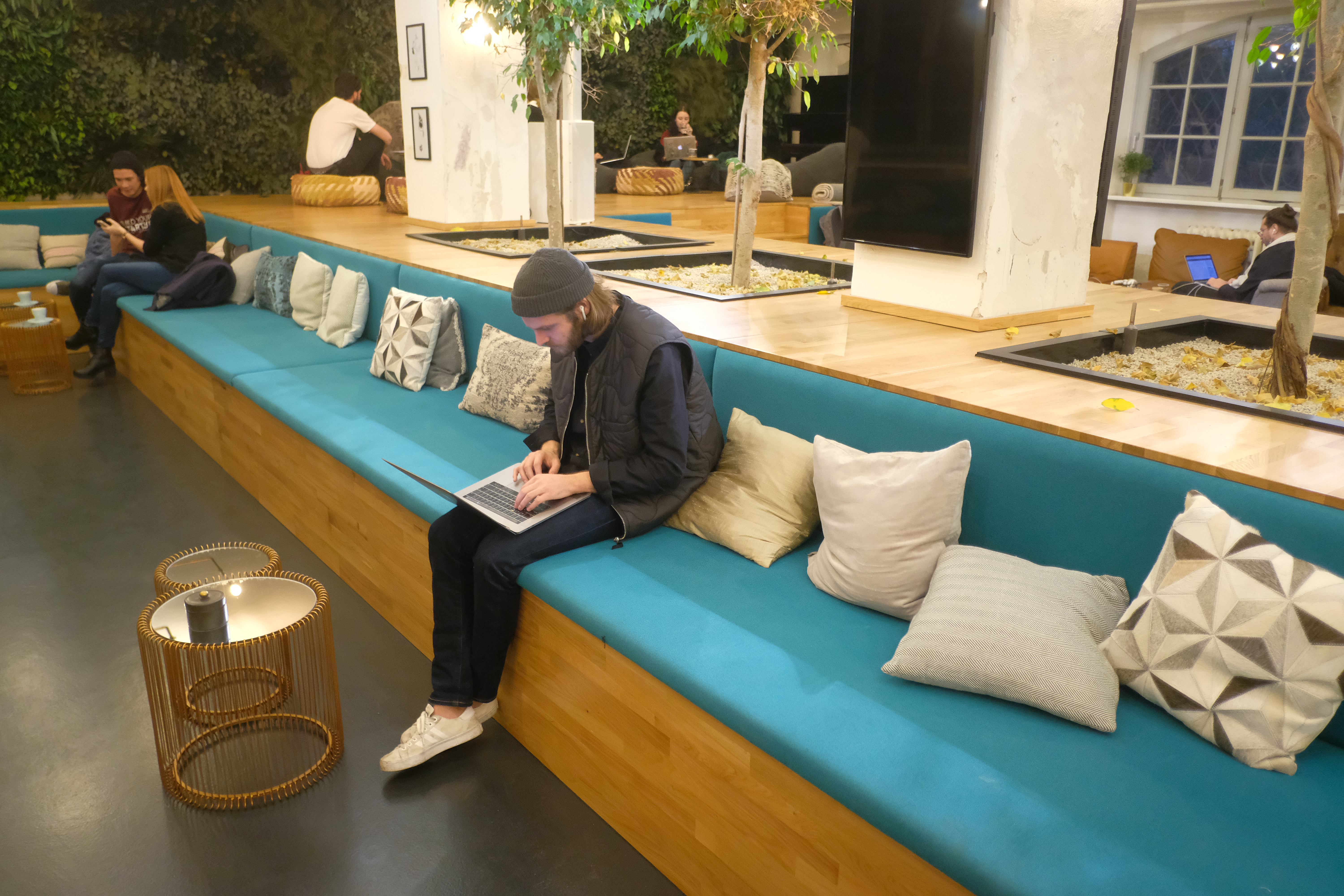 A man sits on a long bench, looking at his laptop.