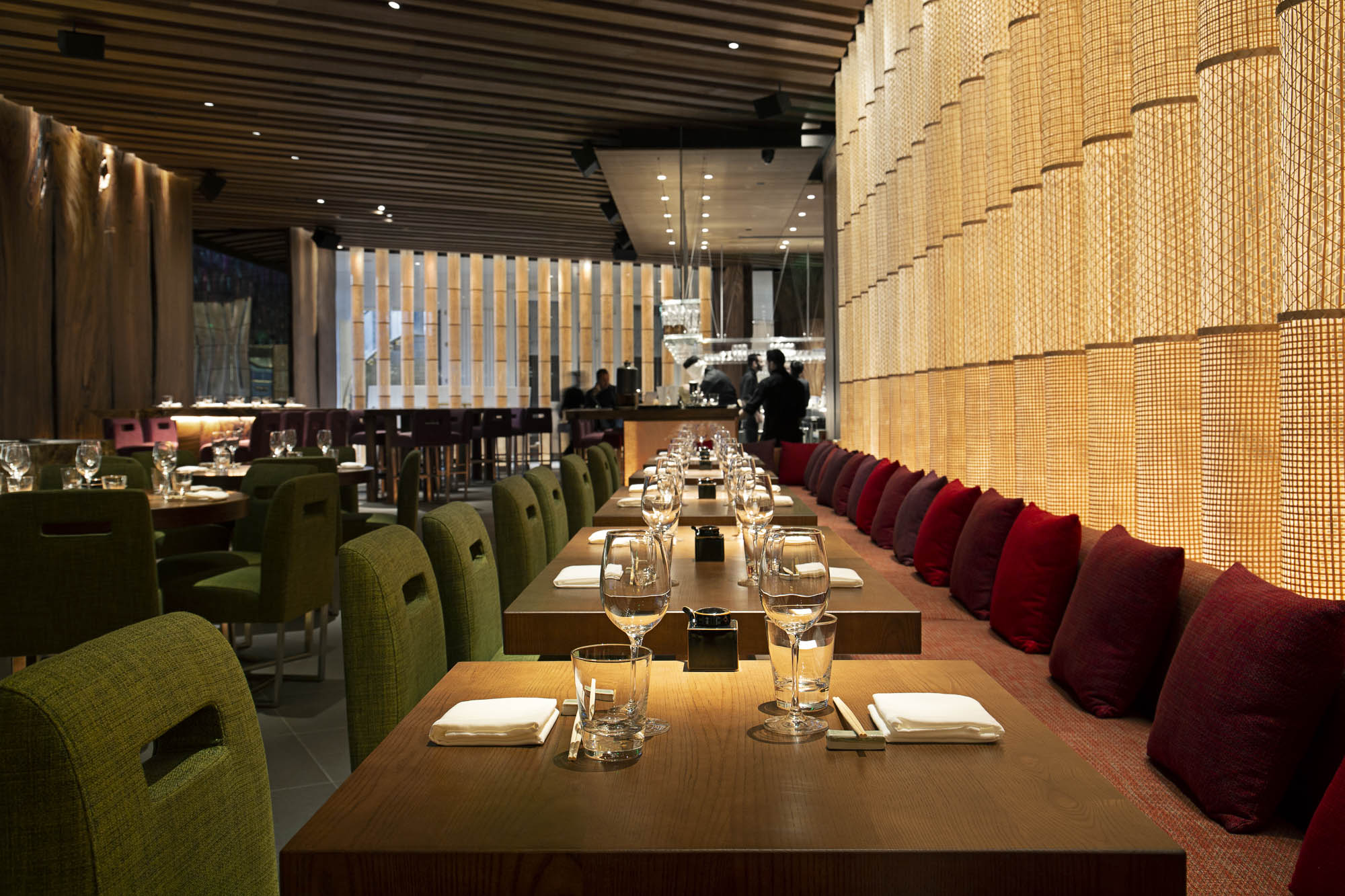 Interior restaurant photo showing an upscale space with plush dark red pillows lining a banquette, lots of slats of light wood, and light wood tables