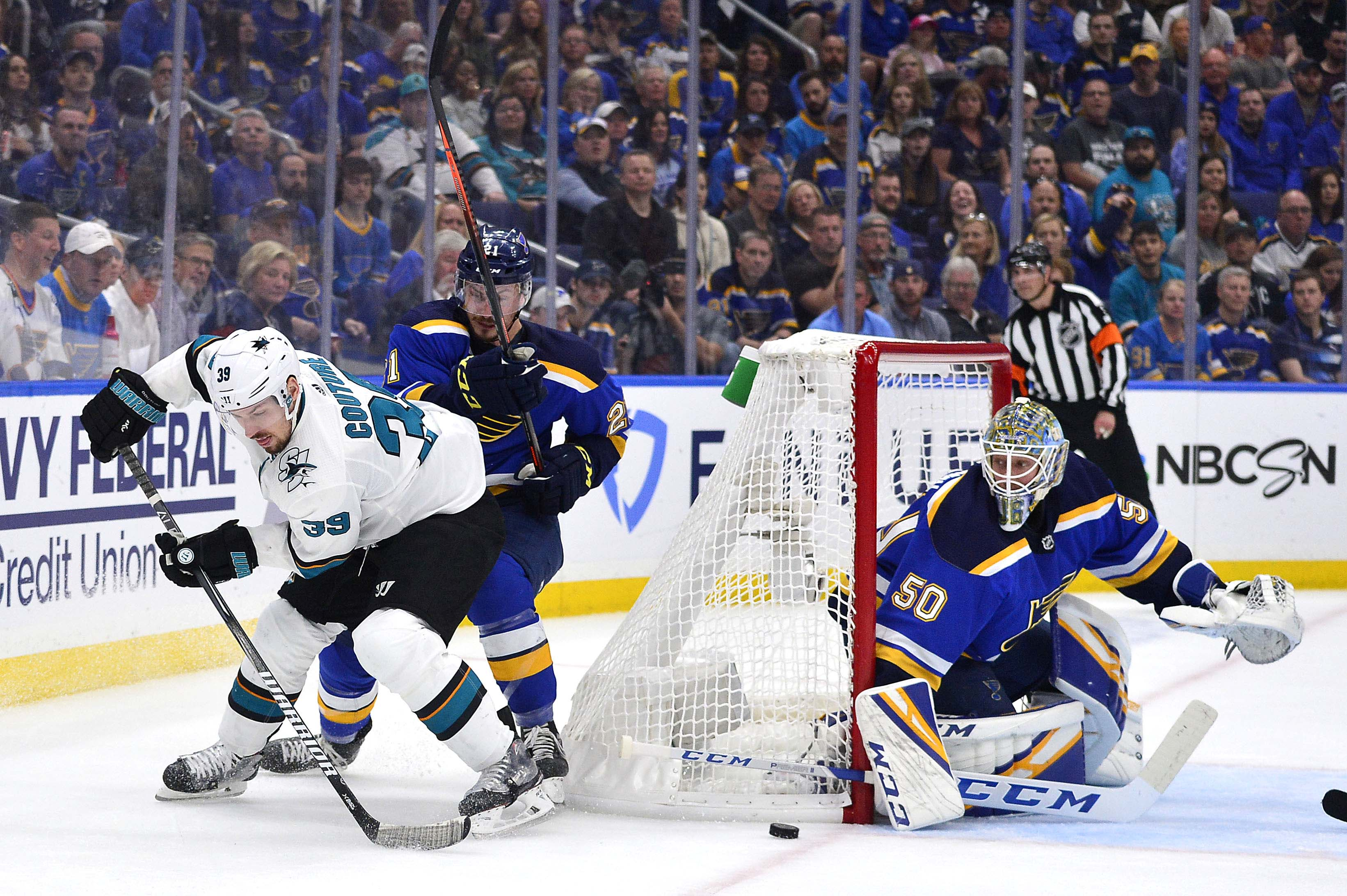May 17, 2019; St. Louis, MO, USA; San Jose Sharks center Logan Couture (39) handles the puck as St. Louis Blues goaltender Jordan Binnington (50) and center Tyler Bozak (21) defend during the first period in game four of the Western Conference Final of th