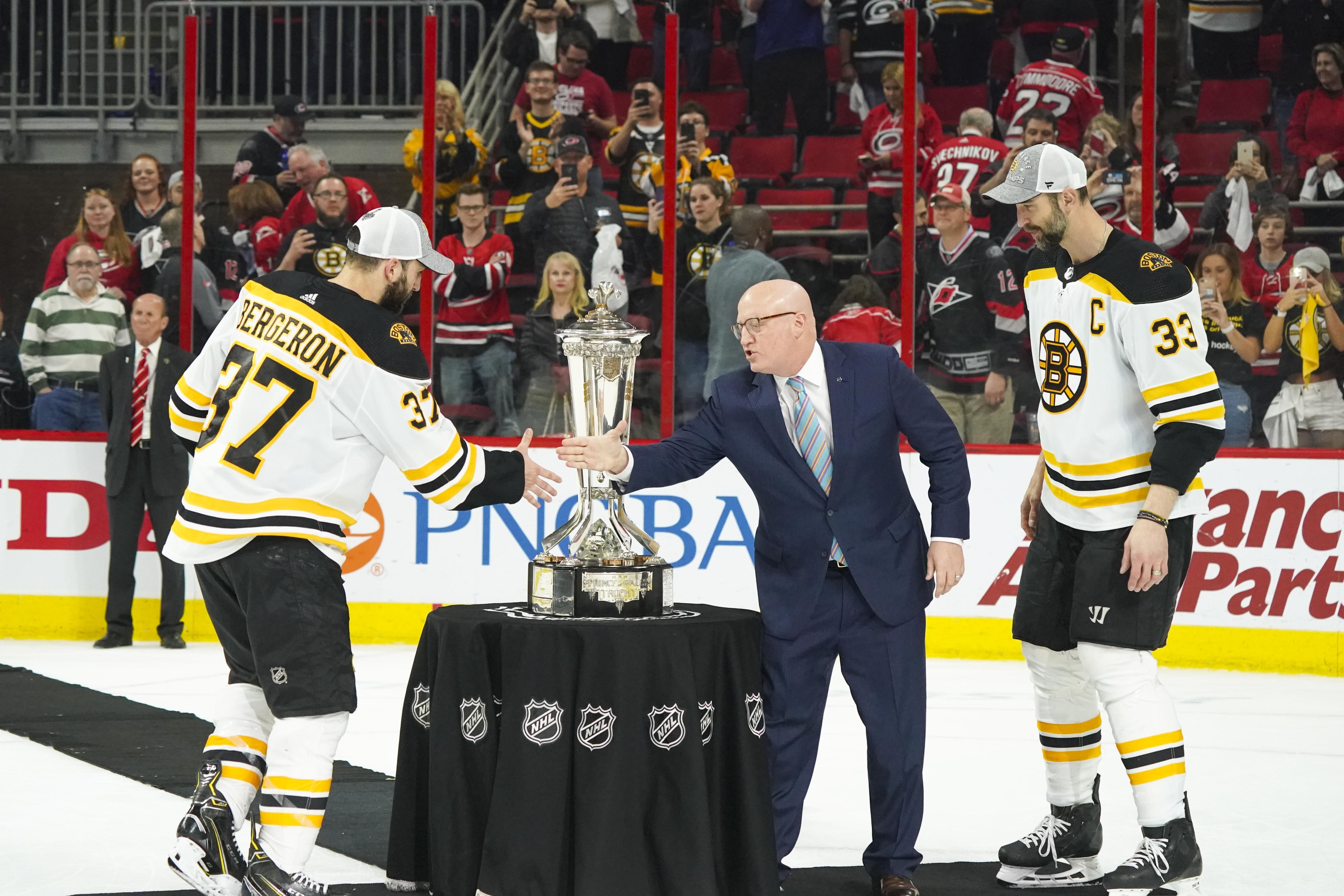 May 16, 2019; Raleigh, NC, USA; Boston Bruins center Patrice Bergeron and defenseman Zdeno Chara are congratulated by NHL deputy Commissioner Bill Daly after defeating the Carolina Hurricanes in Game 4 of the Eastern Conference Final of the 2019 Stanley C