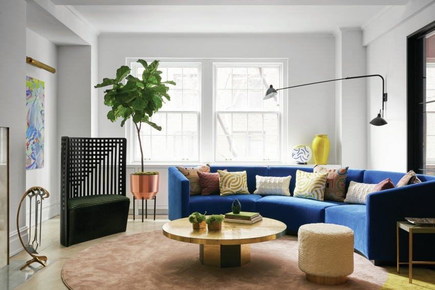 A living area with a blue couch, table, chairs, plants, and large windows letting in natural light.