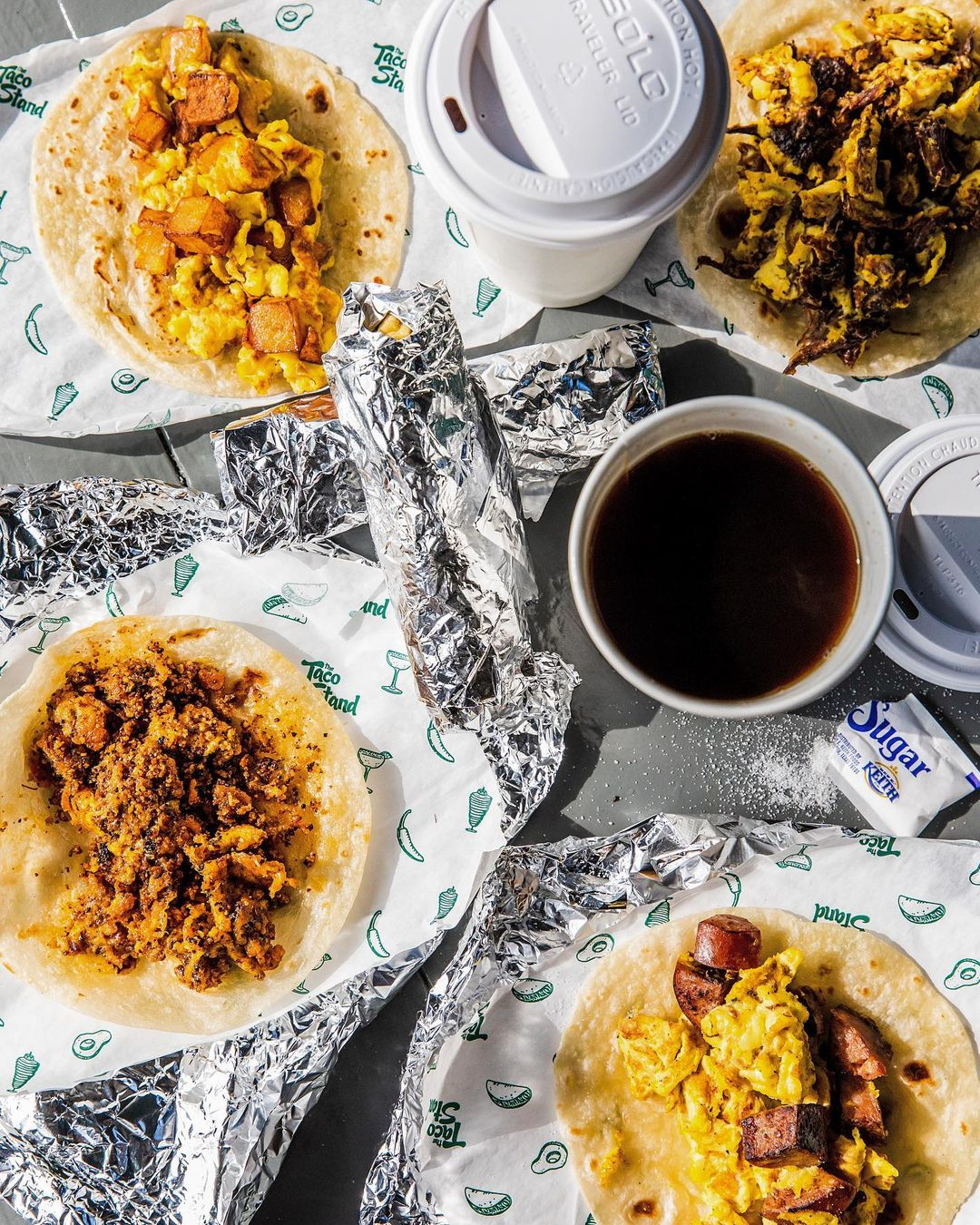 a spread of breakfast tacos on top of foil surrounded bu styrofoam cups of coffee