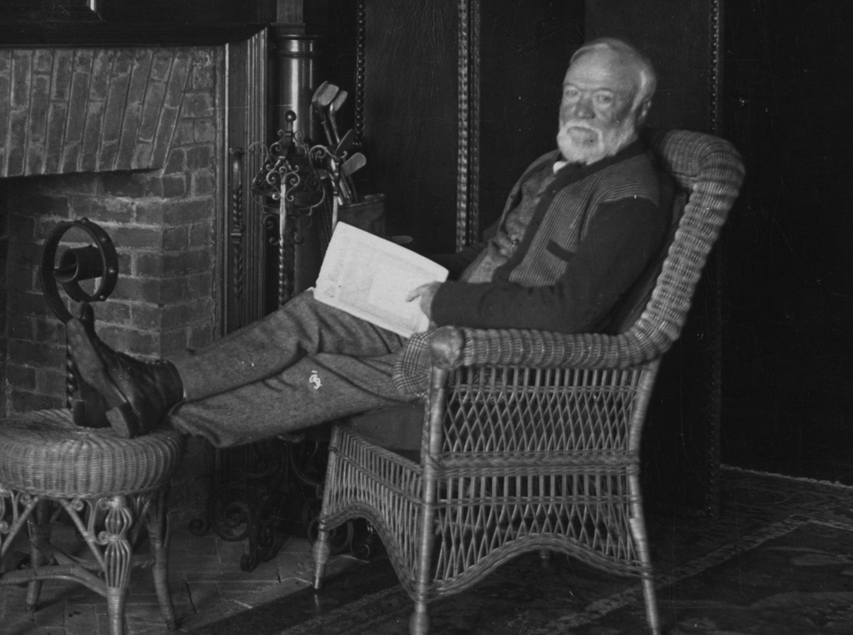 Andrew Carnegie holds an open book and sits in a rattan chair with his feet up by a fireplace as he poses for a portrait in 1913.