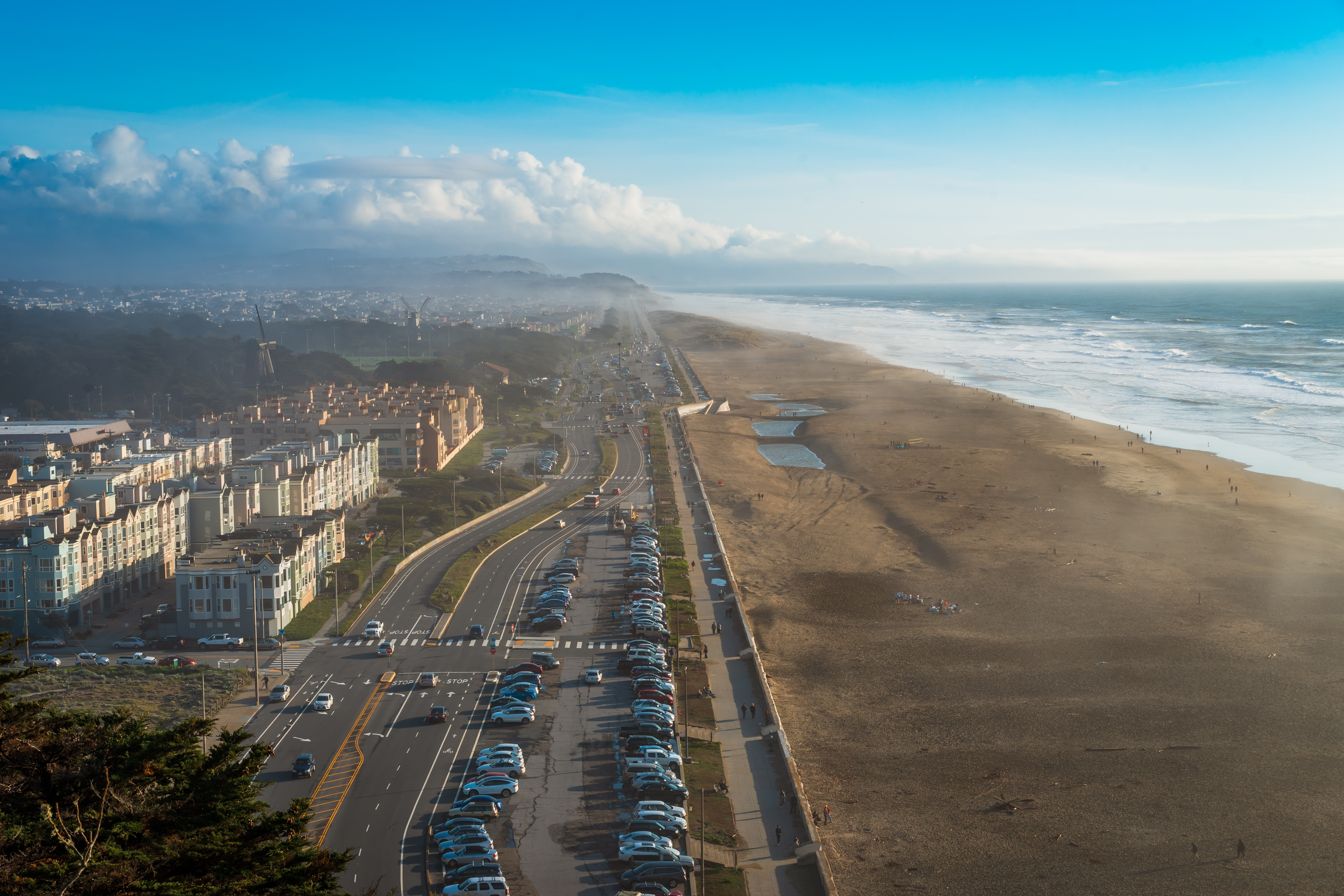 A long stretch of sandy beach with residential units on the left, the ocean on the right. Fog and clouds can also be seen in the distance.