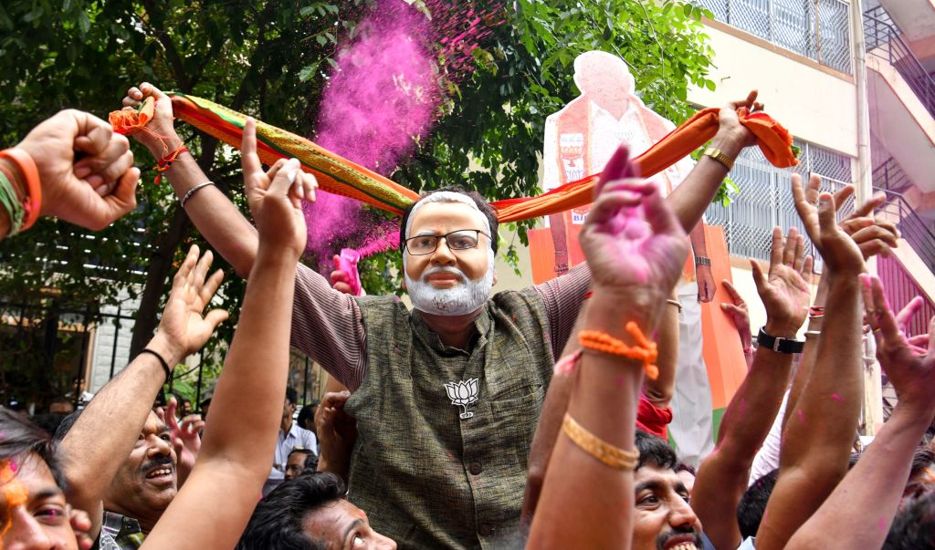 A supporter of the Bharatiya Janata Party (BJP) wearing a mask of Indian Prime Minister Narendra Modi dances as he celebrates on the vote results day for India's general election in Bangalore on May 23, 2019.