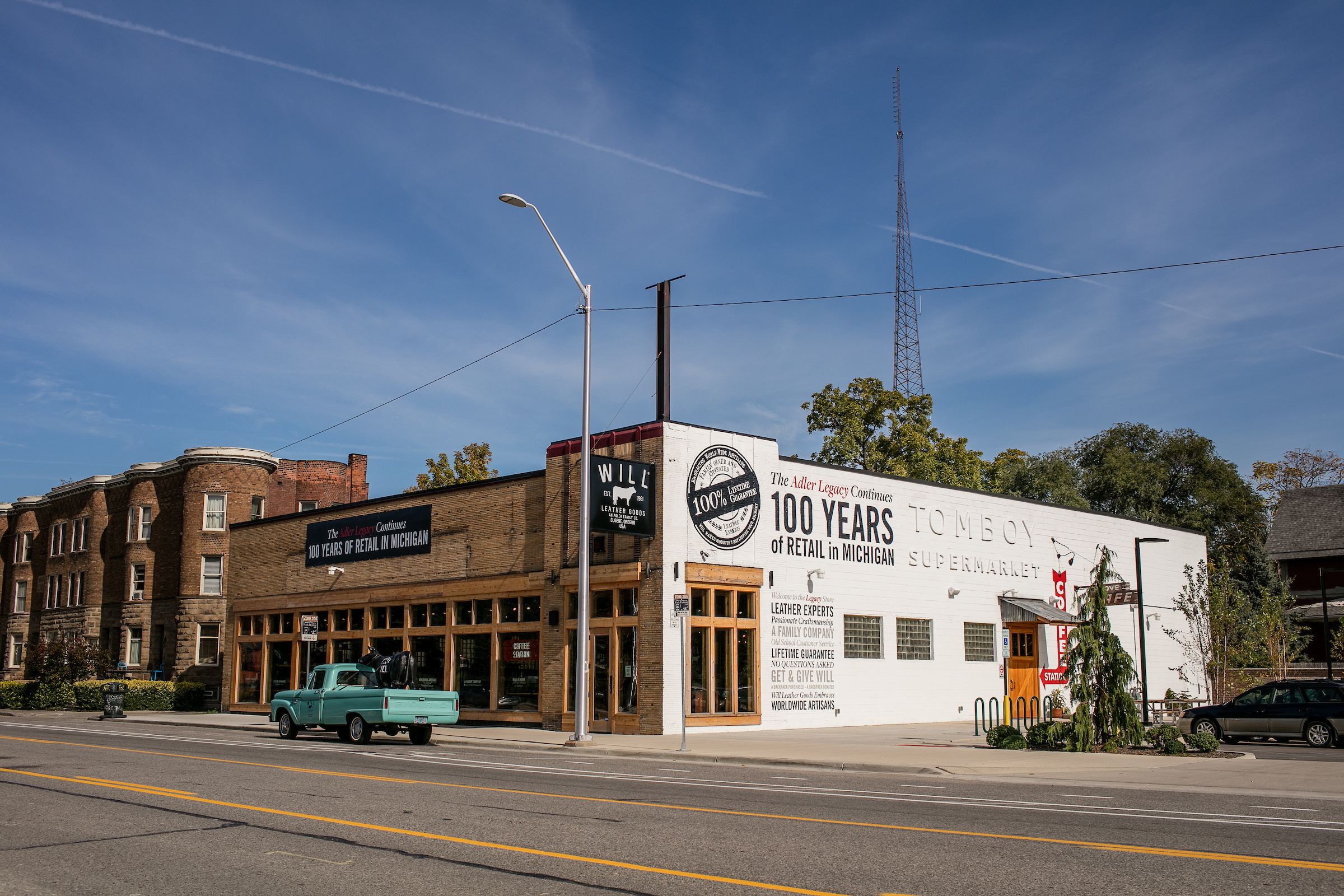Will Leather Goods featured a tan brick facade with wood framed windows and a white painted wall facing the parking lot. A green vintage pickup truck is parked outside Will Leather Goods on a sunny day.