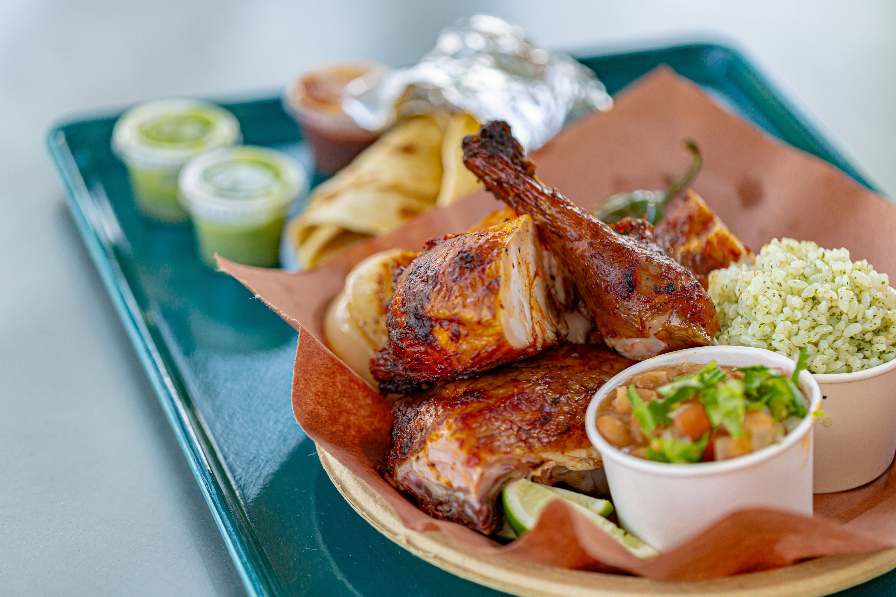 A quarter chicken al carbon at Little Rey with corn or flour tortillas, smoked onions and jalapenos, ranch beans, and cilantro rice