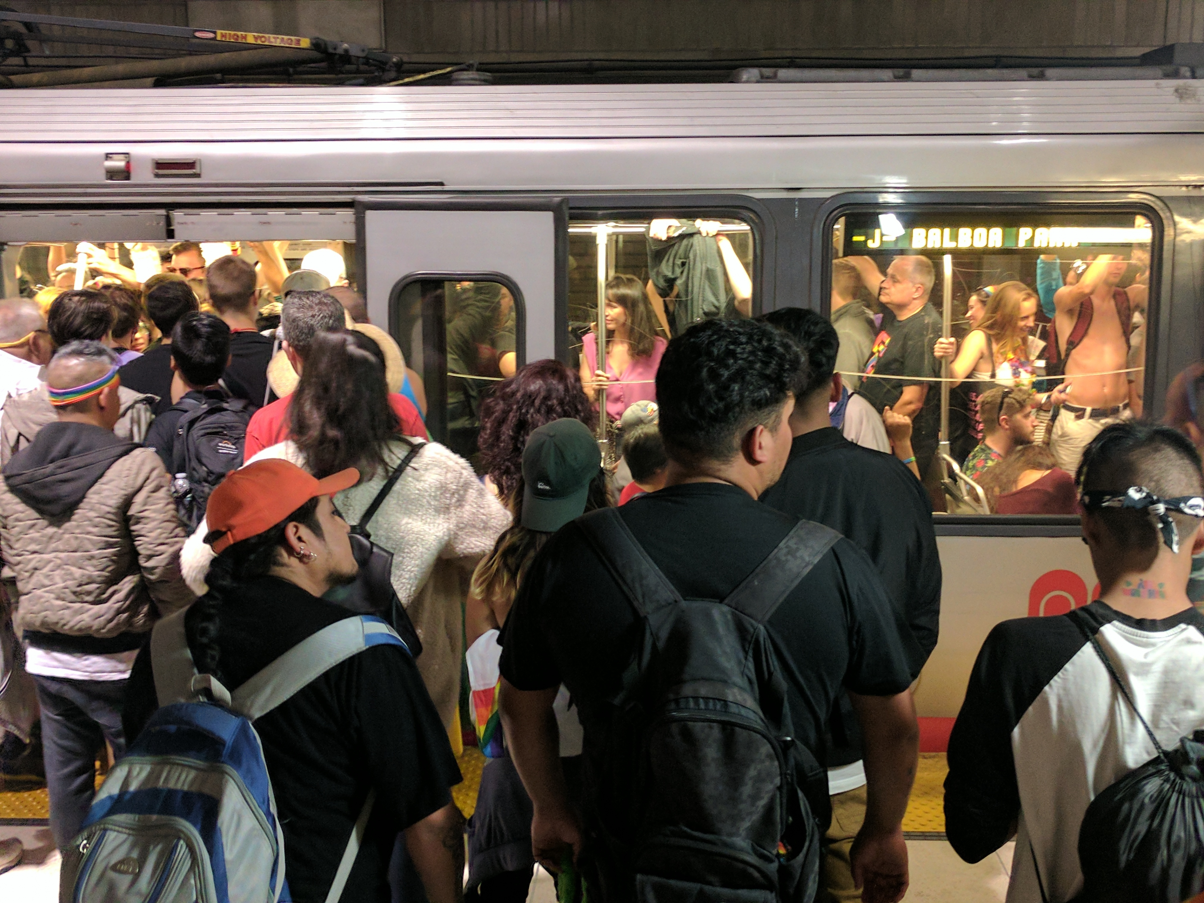 A crowd of people waiting to get on a subway.