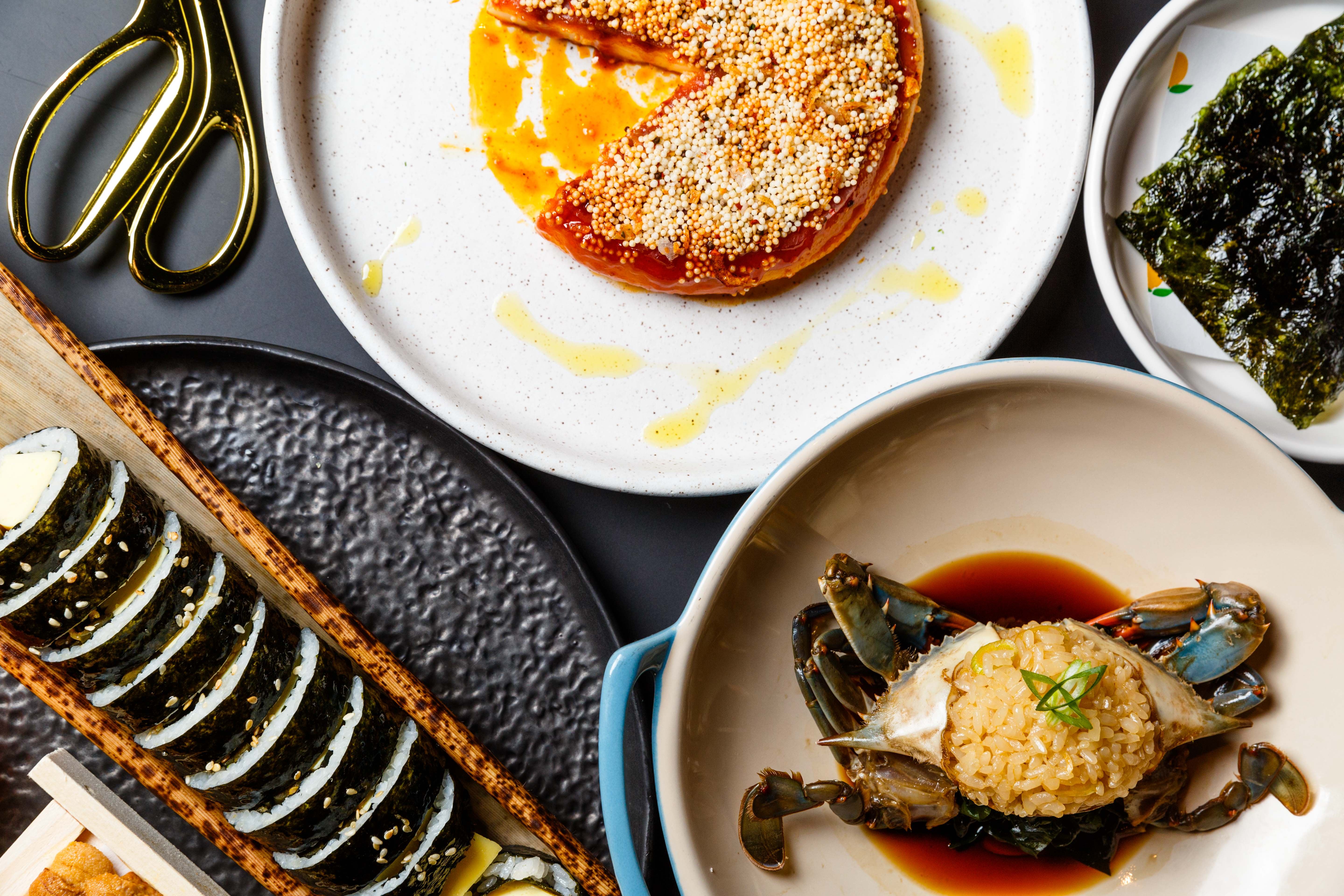 An assortment of dishes at Kawi, including raw blue crab, its shell stuffed with rice, and a pinwheel of roasted rice cake, which is dark red and topped with sesame seeds