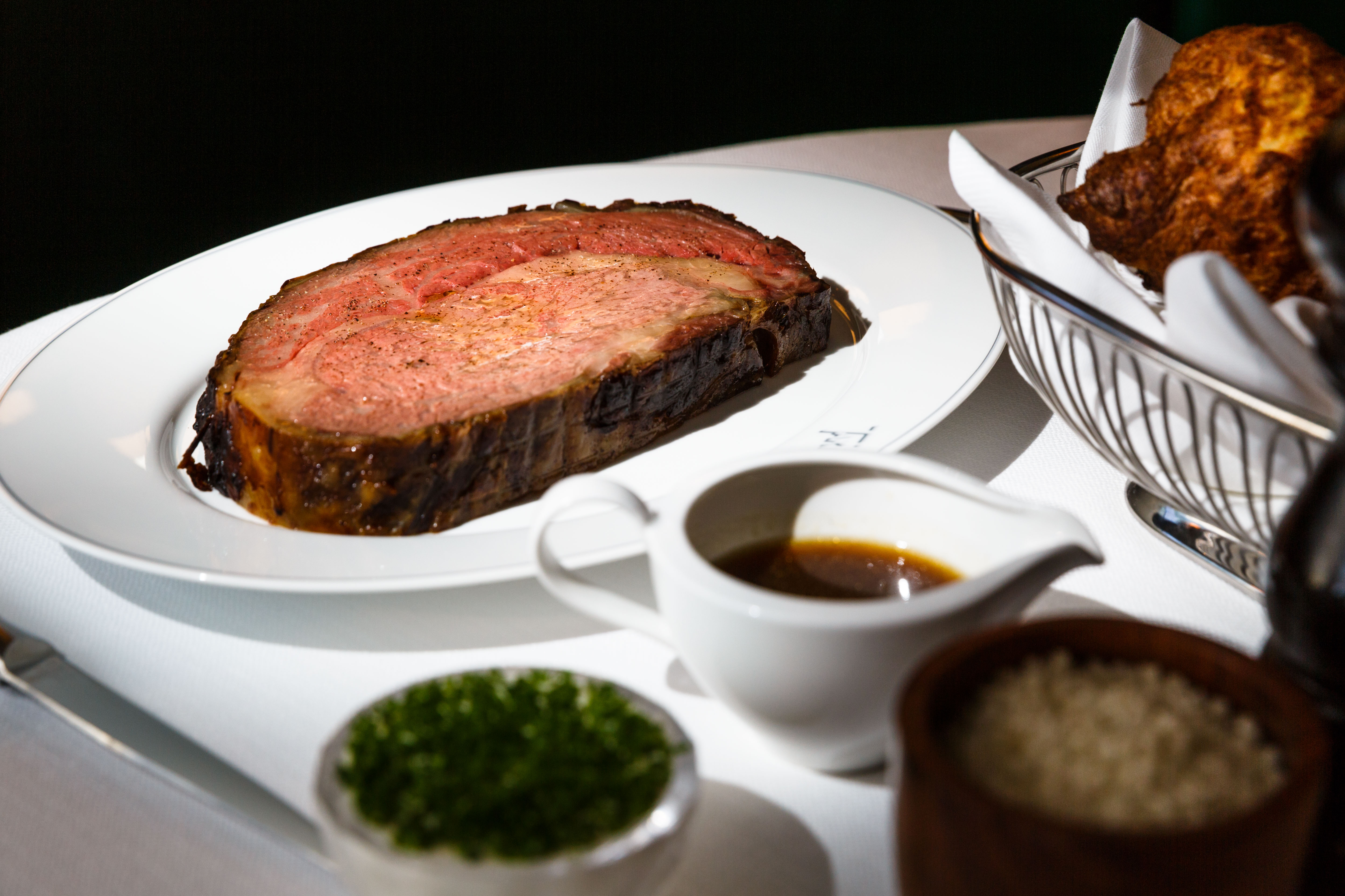 A large, pink prime rib sits on a white plate, with small side dishes in the foreground