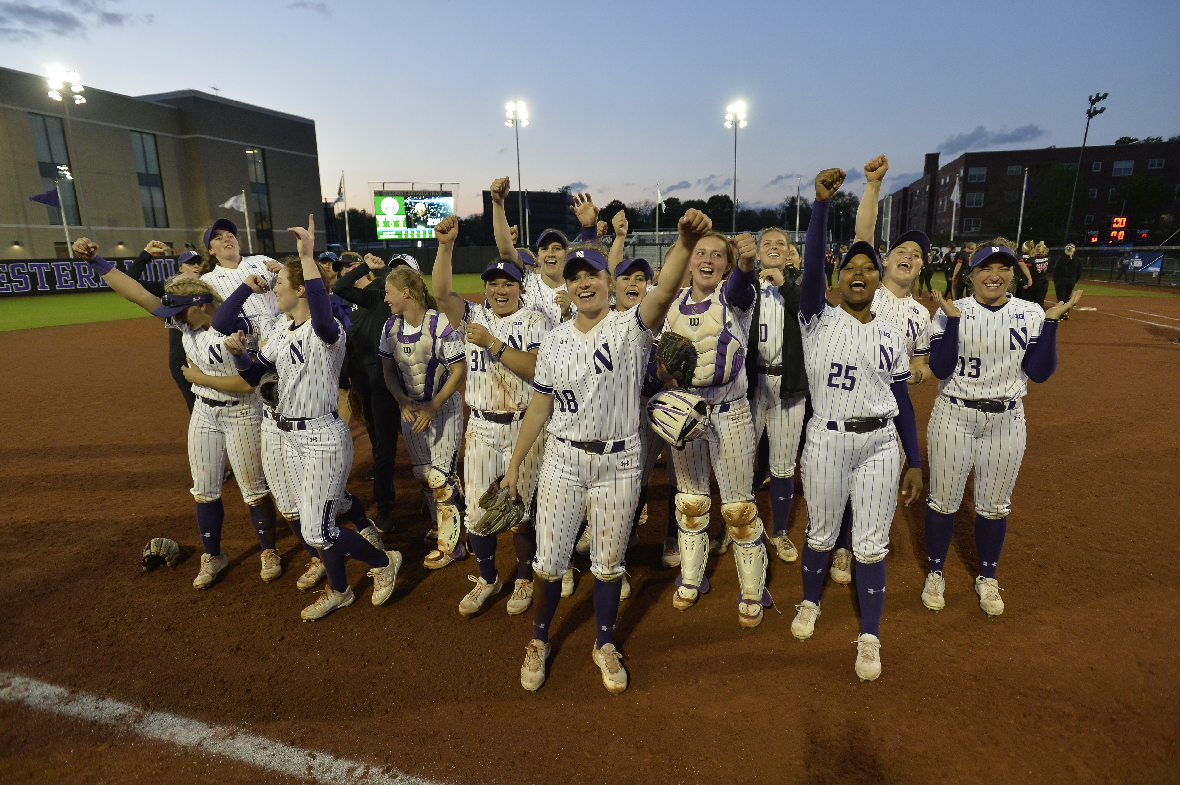 The Northwestern softball team celebrates its victory over the Louisville Cardinals to clinch its berth in the NCAA Super Regionals, Sunday, May 19, at Drysdale Field.