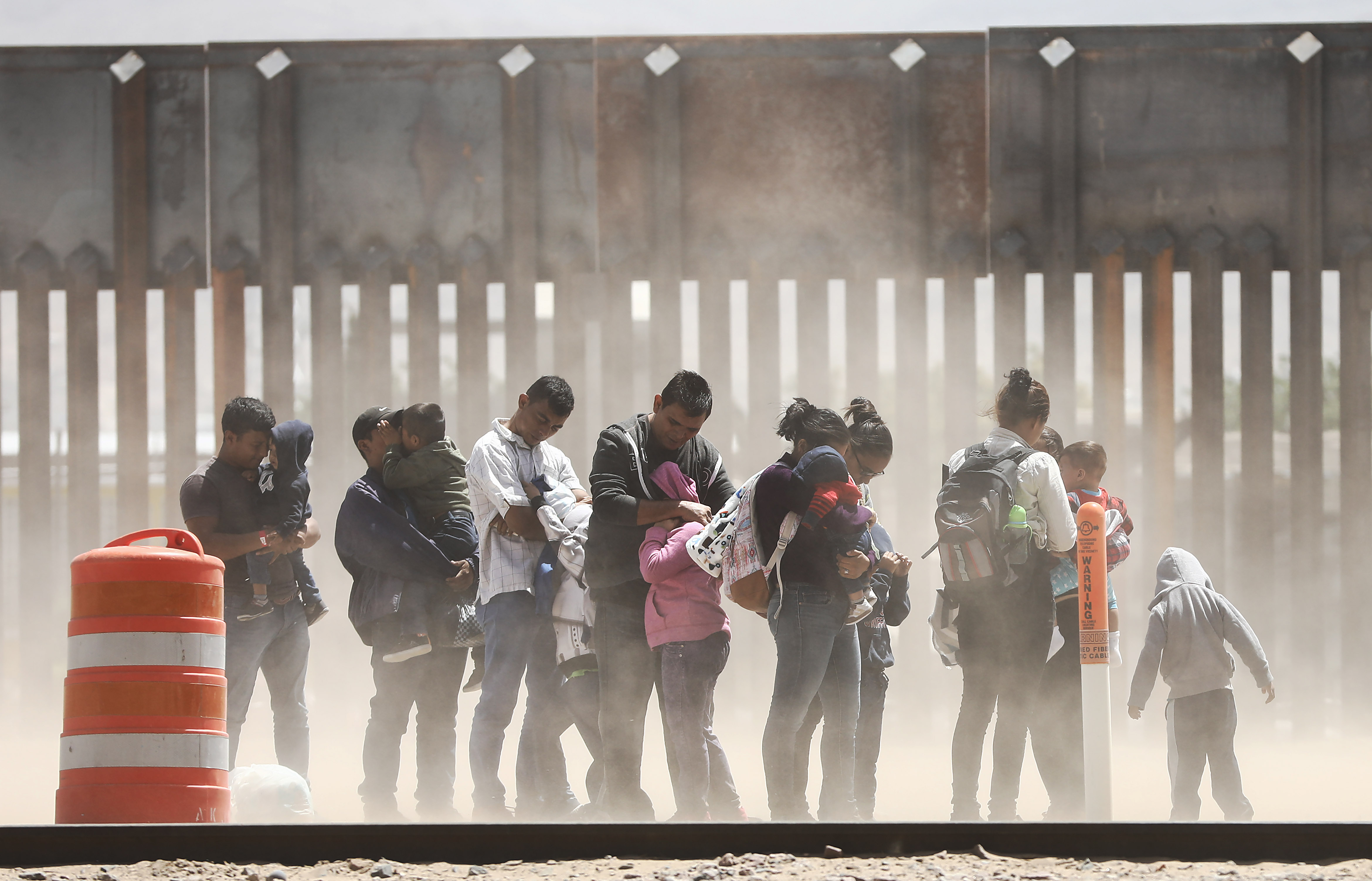 Men, women, and children endure a cloud of dust in front of the US-Mexico border wall in Texas.