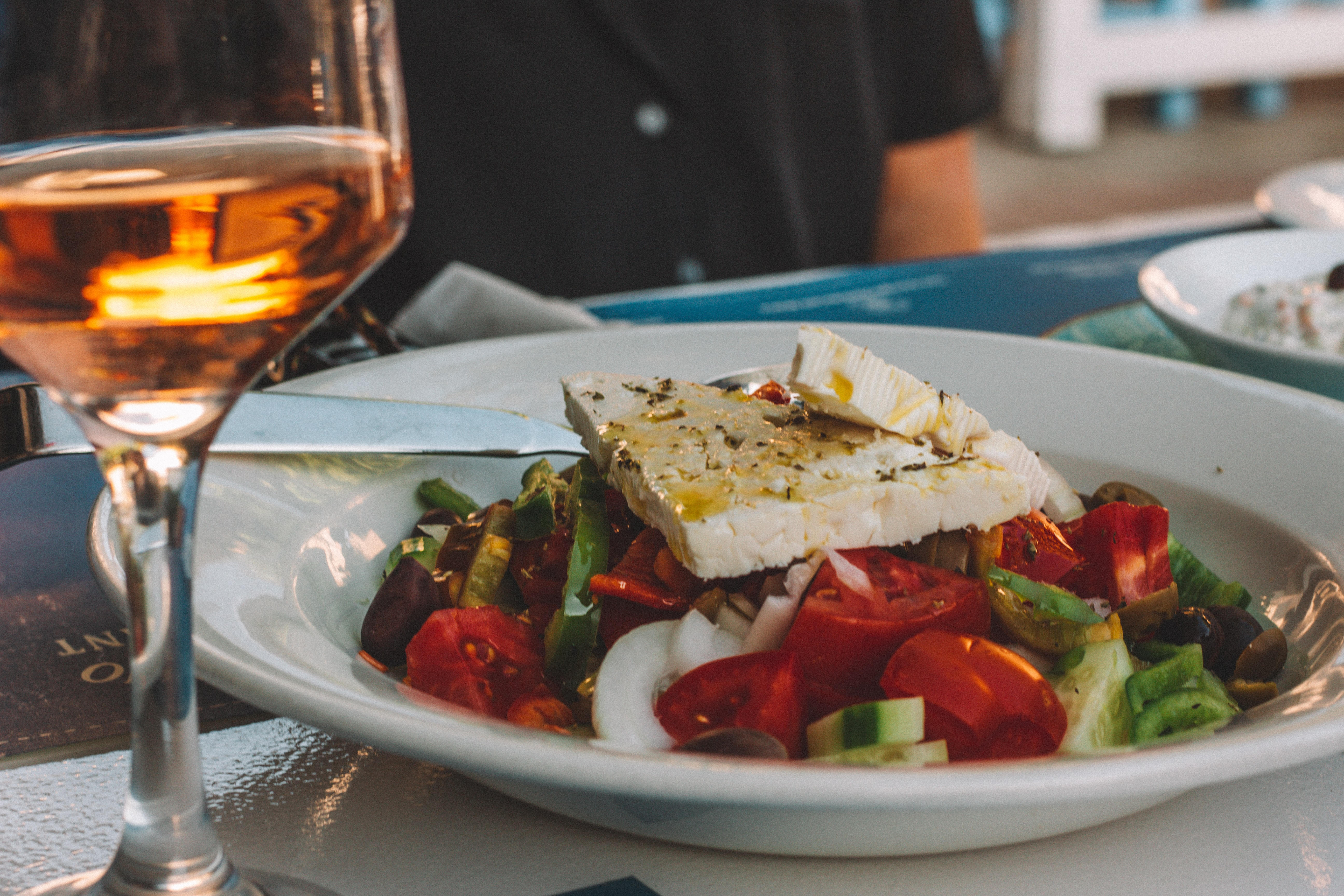 Close up of cheese on top of salad with wine in the foreground