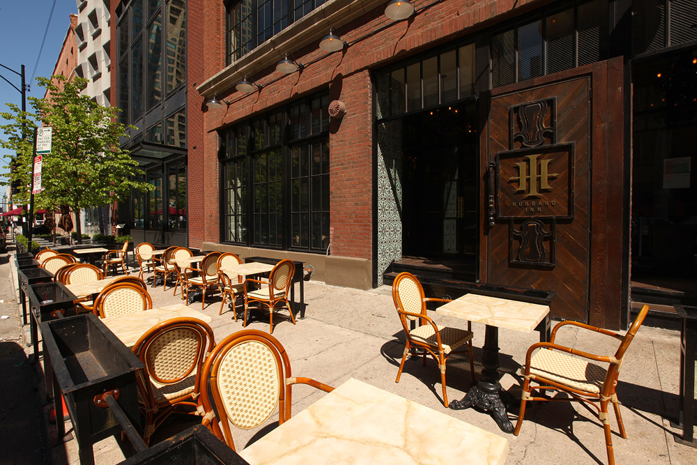 """Sidewalk seating outside of a restaurant with a big """"H"""" outside."""