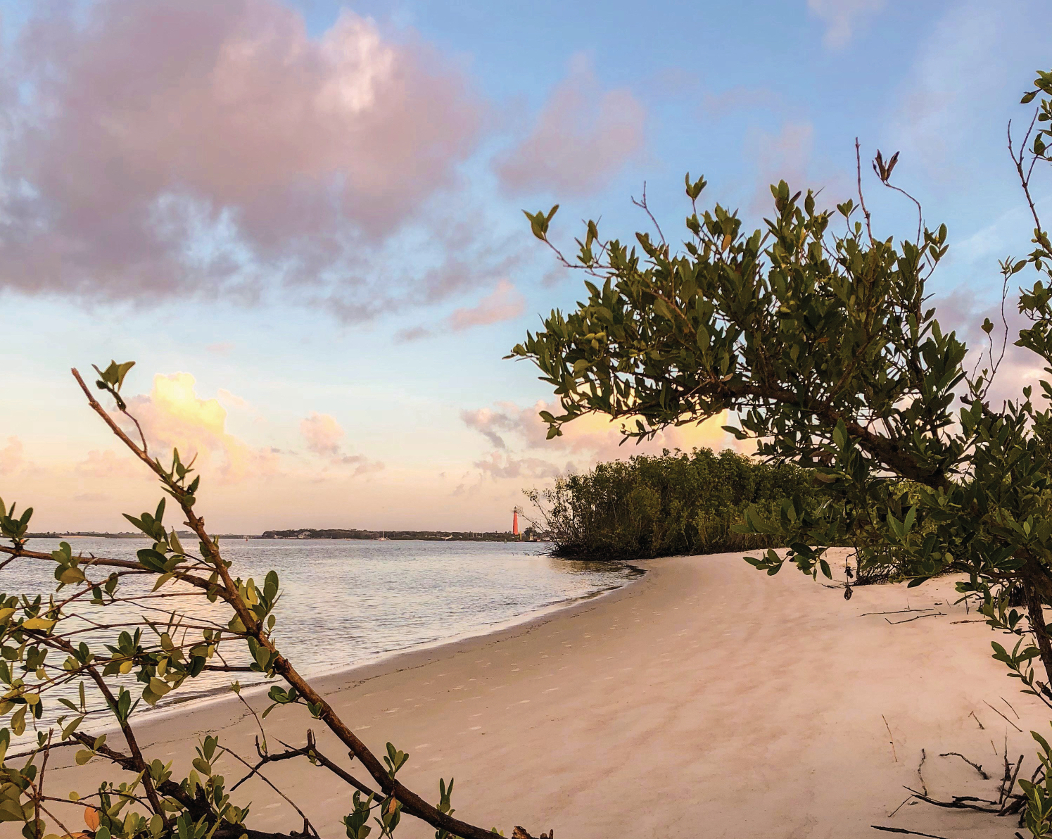 A sandy beach is in the foreground. The beach borders a body of water. It is sunset and the sky is purple, peach, and blue.