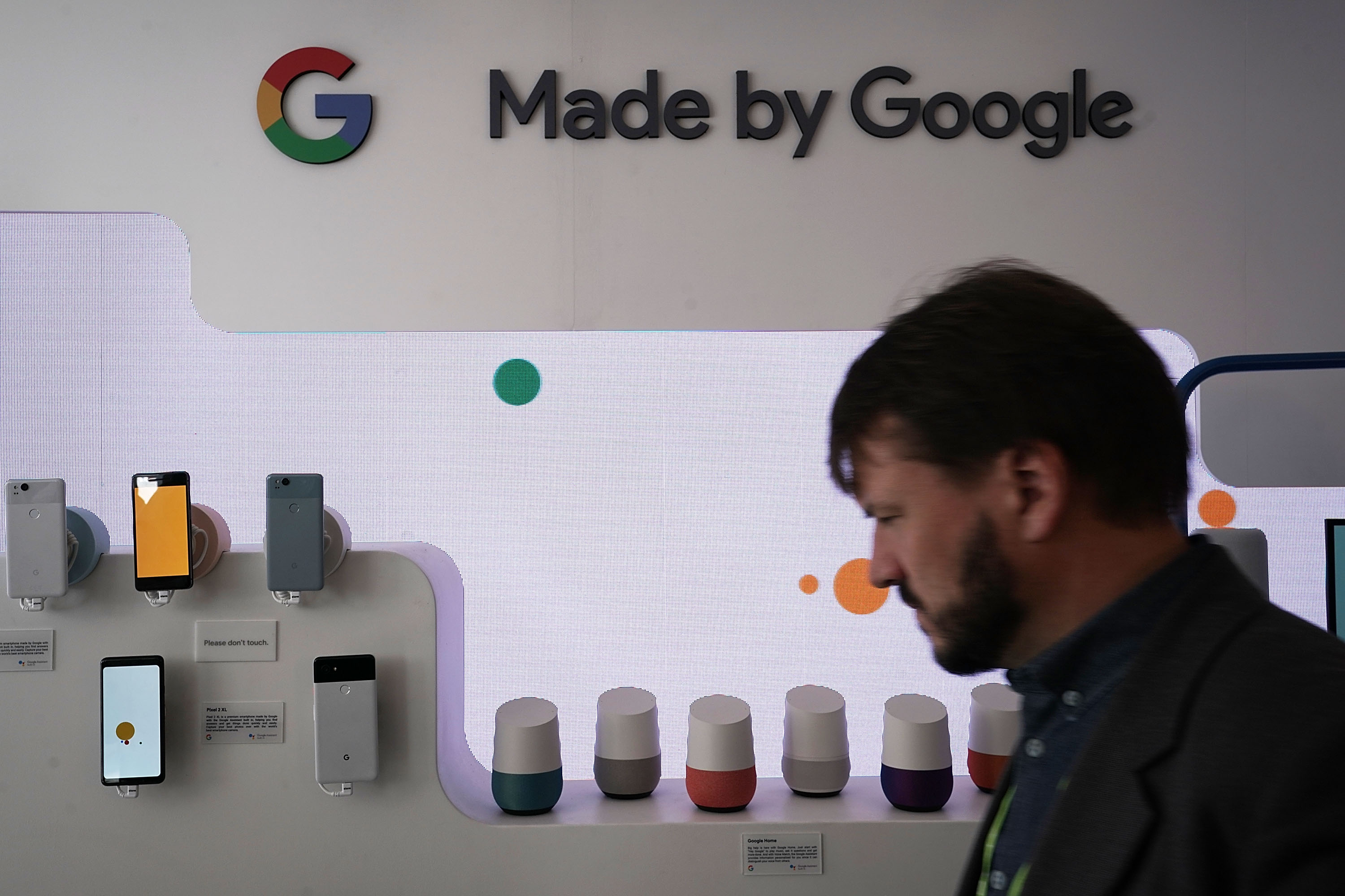 """A man looks at a display of phones and voice assistants """"Made by Google."""""""