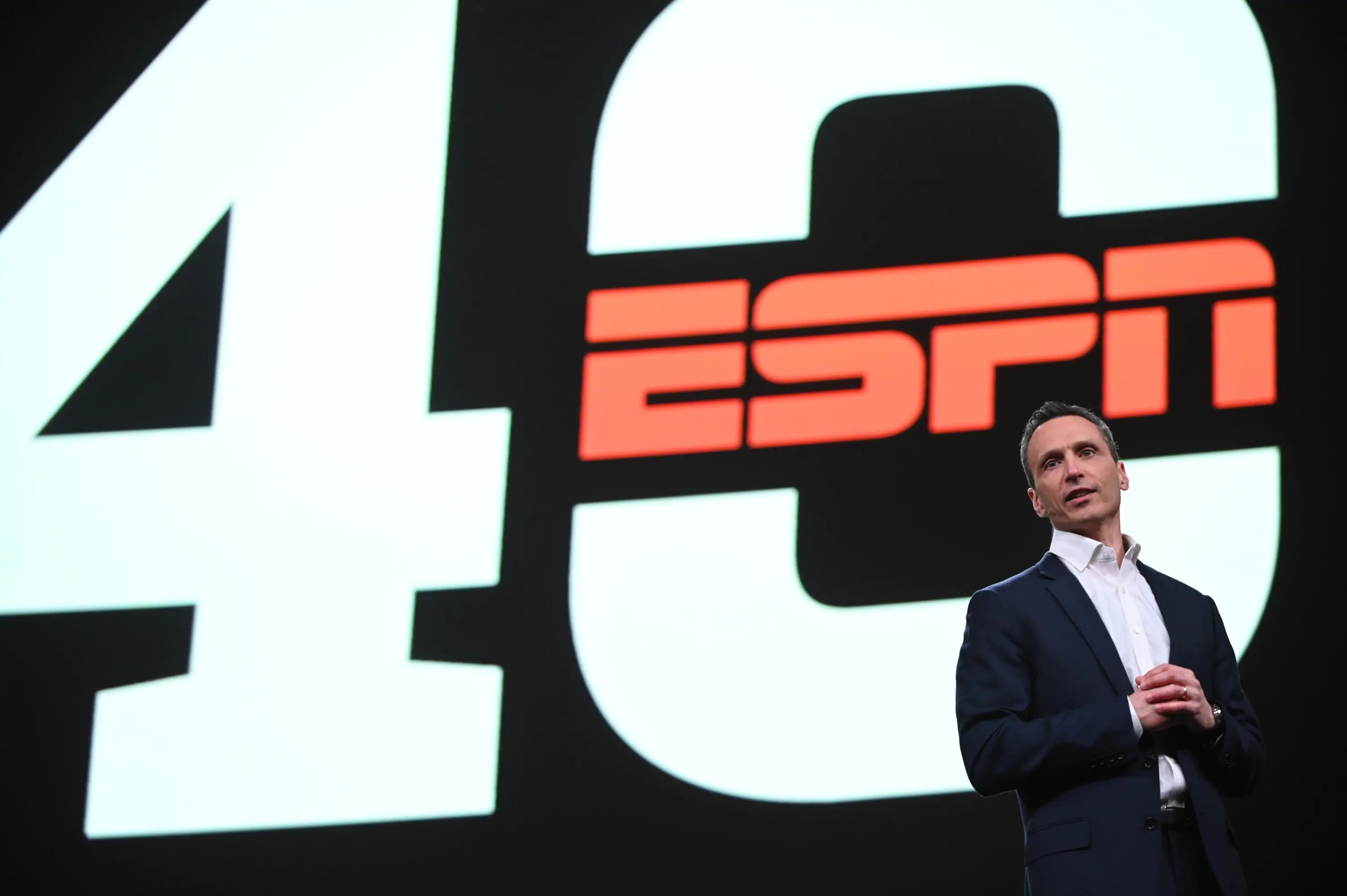 ESPN president Jimmy Pitaro onstage in front of a graphic for ESPN 40.