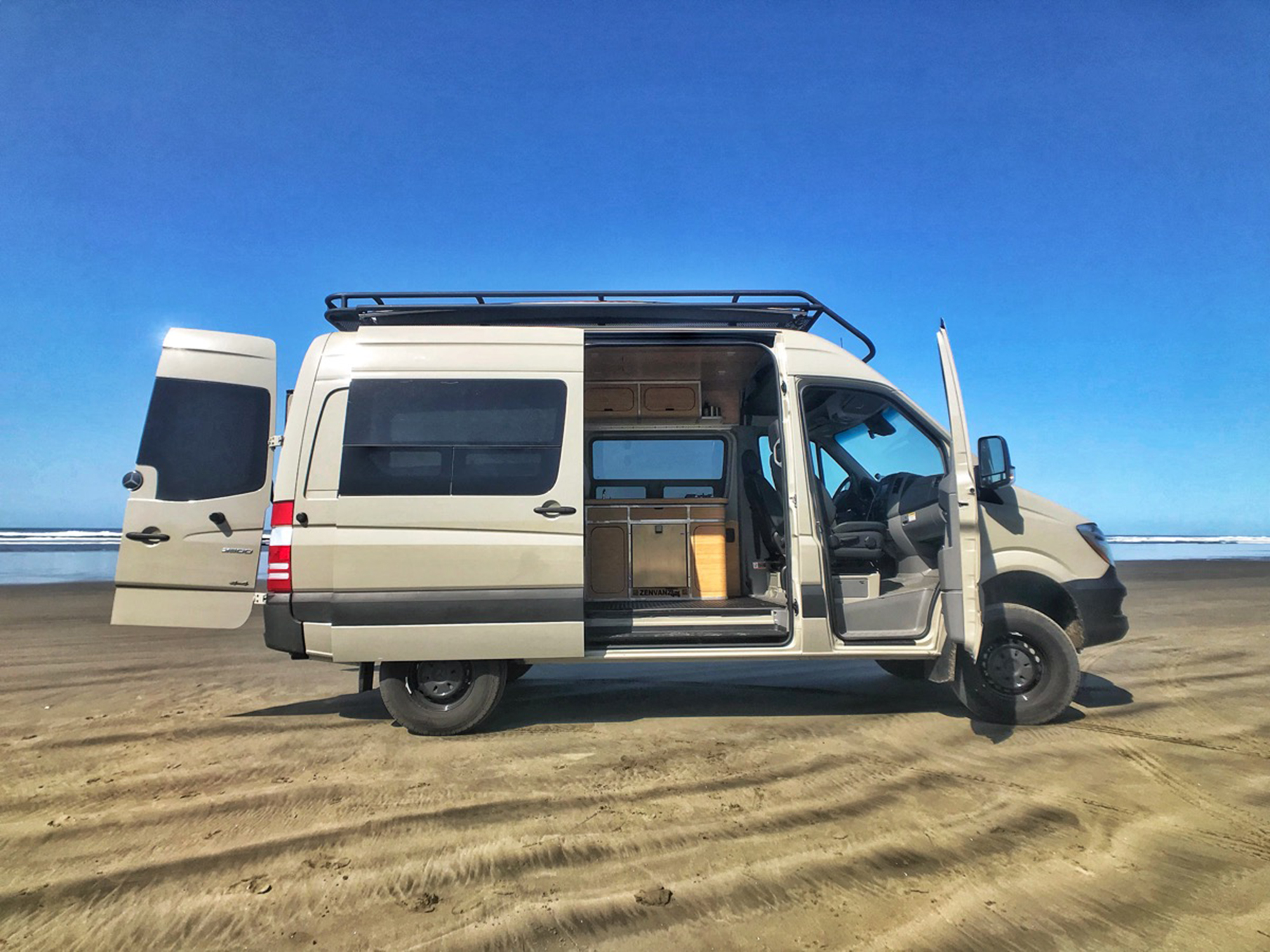 A tan van parked in sand. The doors of the van are open revealing an interior that has a kitchenette.