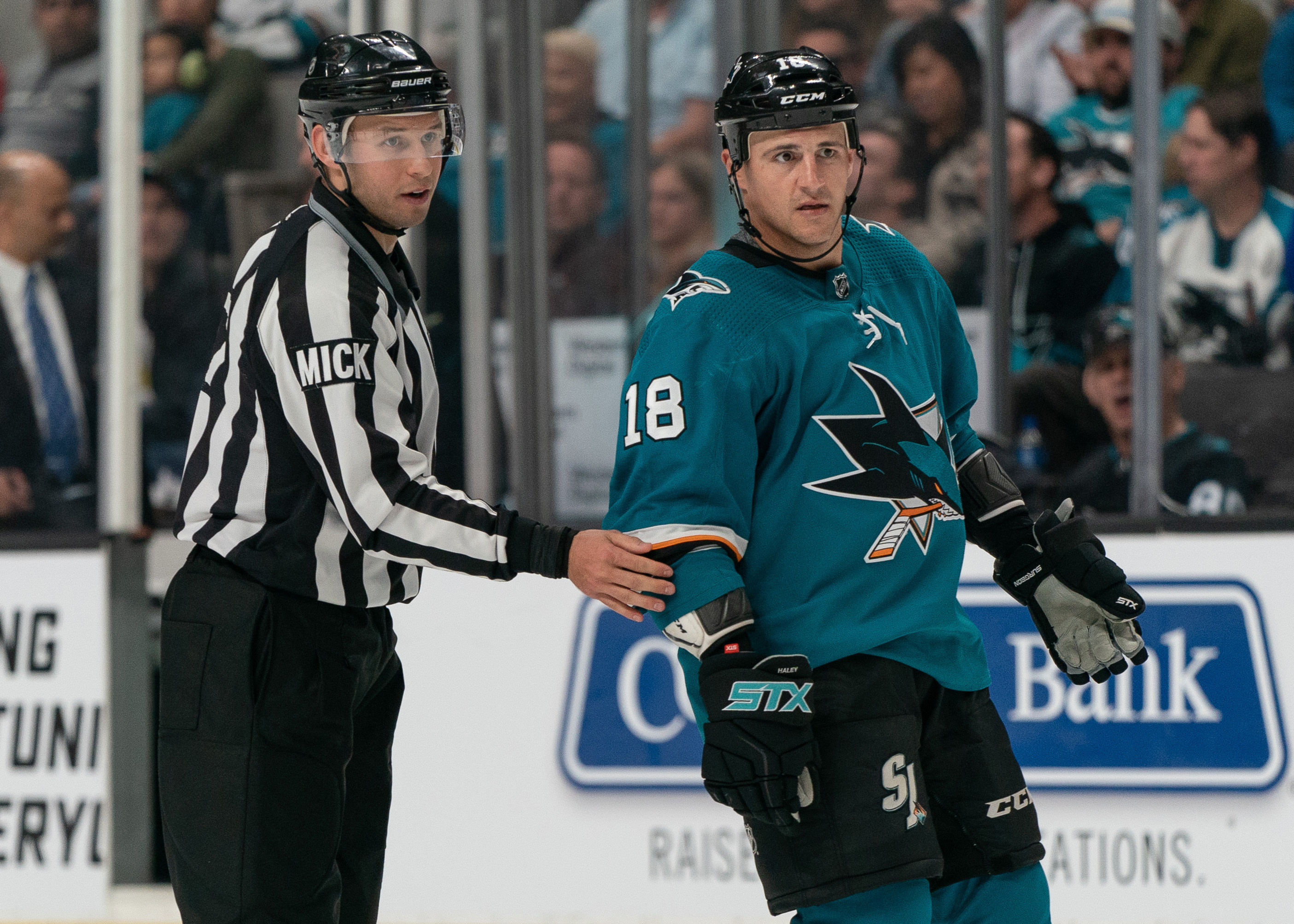 Mar 31, 2019; San Jose, CA, USA; San Jose Sharks center Micheal Haley (18) is escorted off the ice by the linesman Bryan Pancich (94) during the third period for fighting at SAP Center at San Jose.