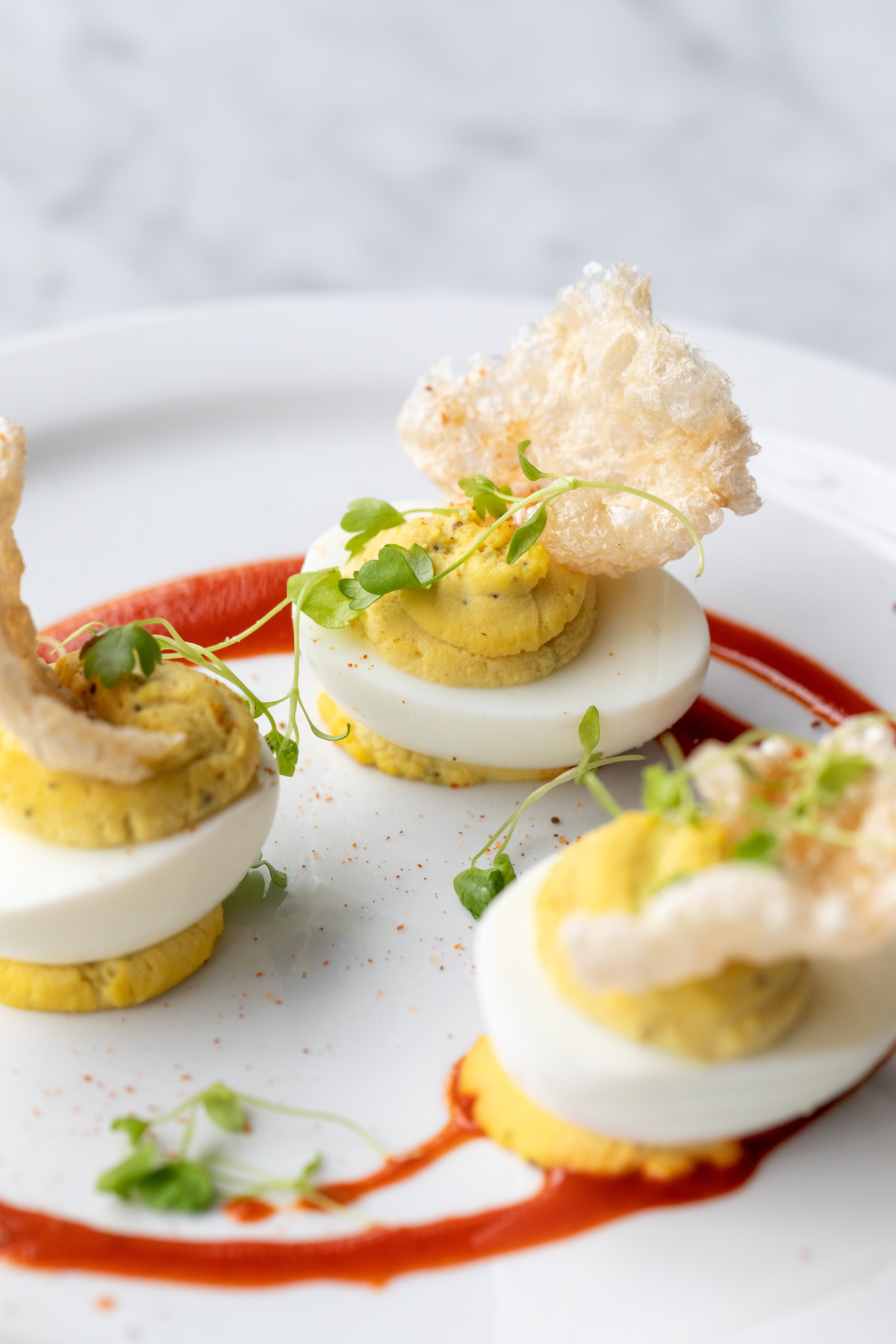 A deviled egg on a plate with pea shoots and pork rinds.