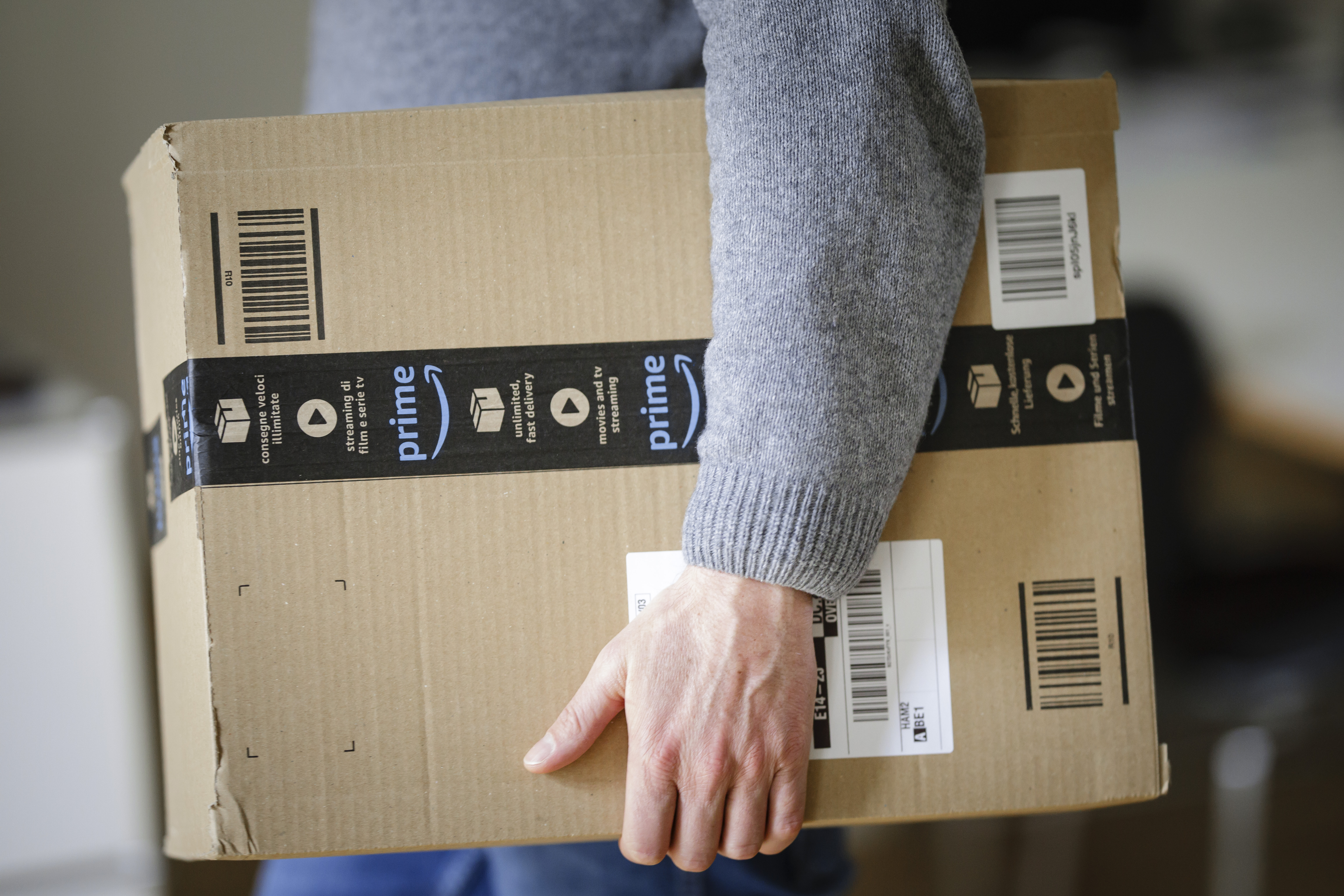 A person carries an Amazon Prime-branded package under their arm.