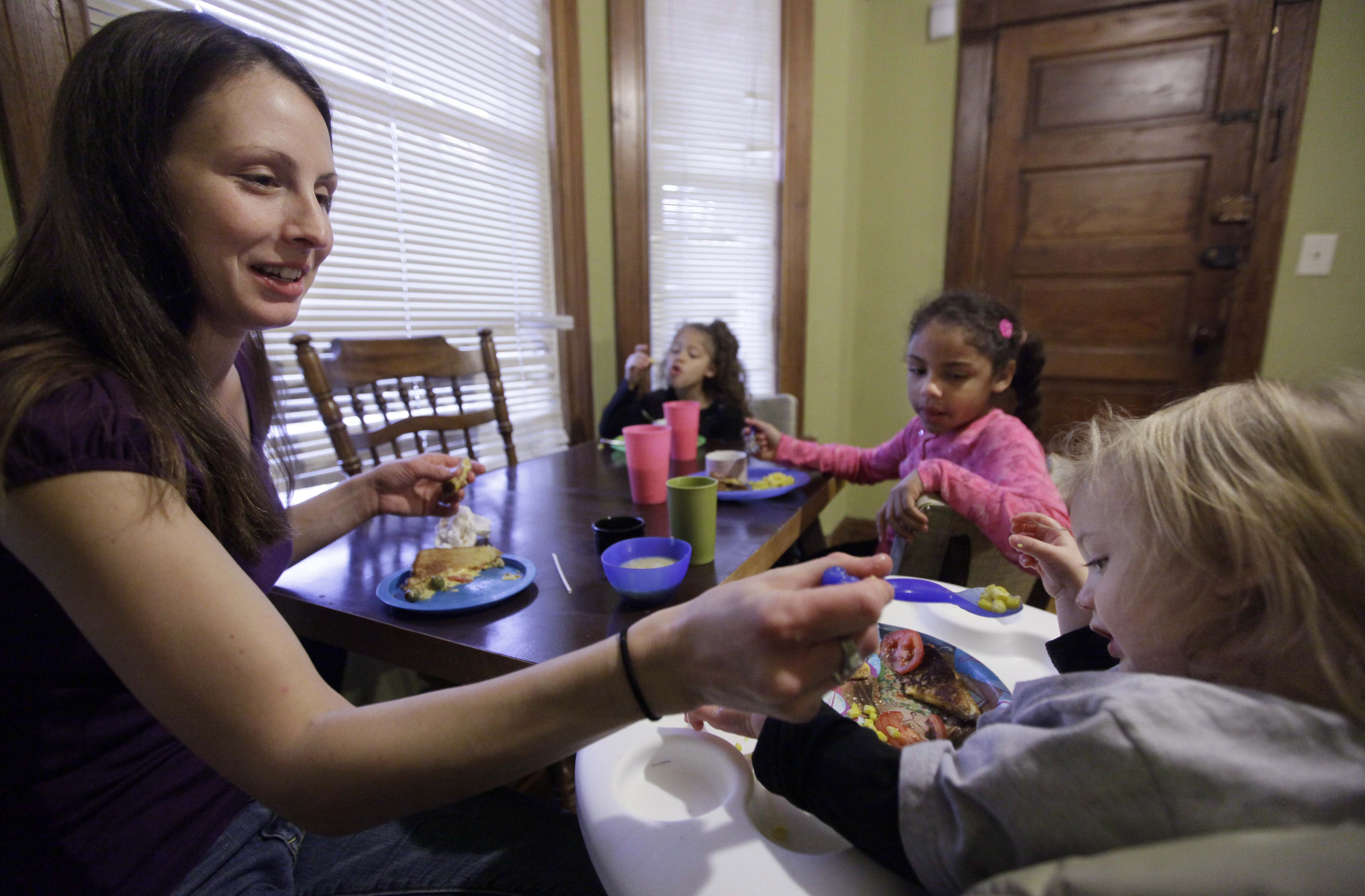 A woman sits at a dinner table with her three children.