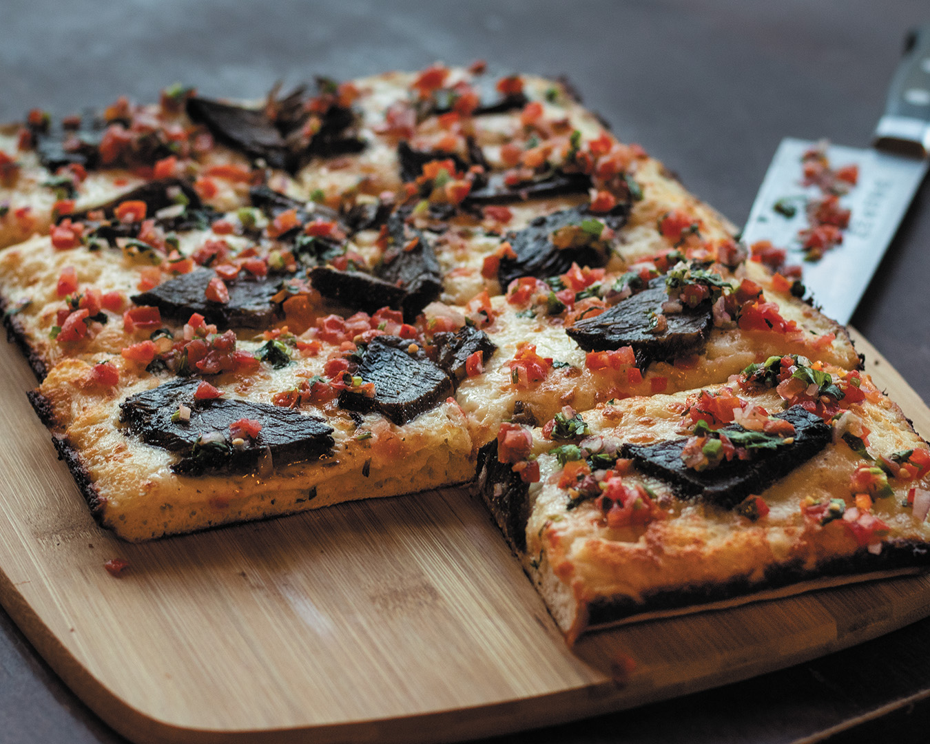 A Detroit-style pizza, with one slice missing, on a wooden cutting board