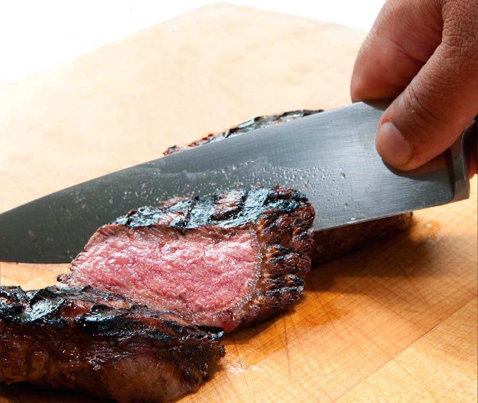 A chef's knife cuts through a slice of rare, charred steak