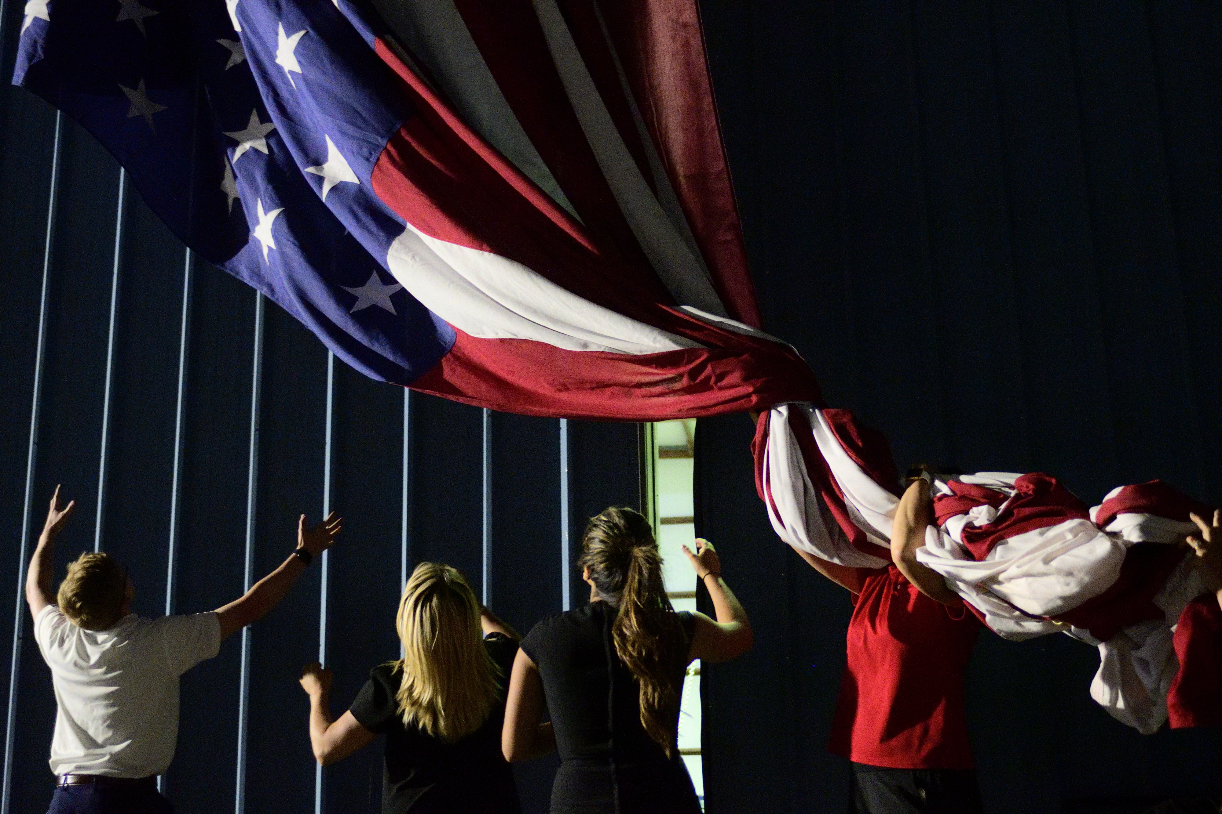 Several people help to take down from onstage a large decoration in the design of the American flag.