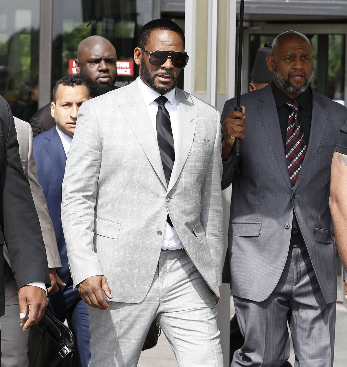 R. Kelly leaves the Leighton Criminal Court Building after appearing before a judge Thursday to face new charges of criminal sexual abuse.
