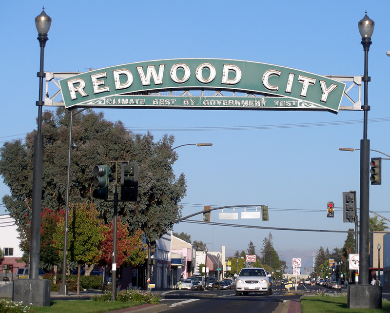 A sign above a street. The sign has these words on it: Redwood City.