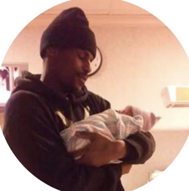 Derrick Cosby, 28, holding one of his three children