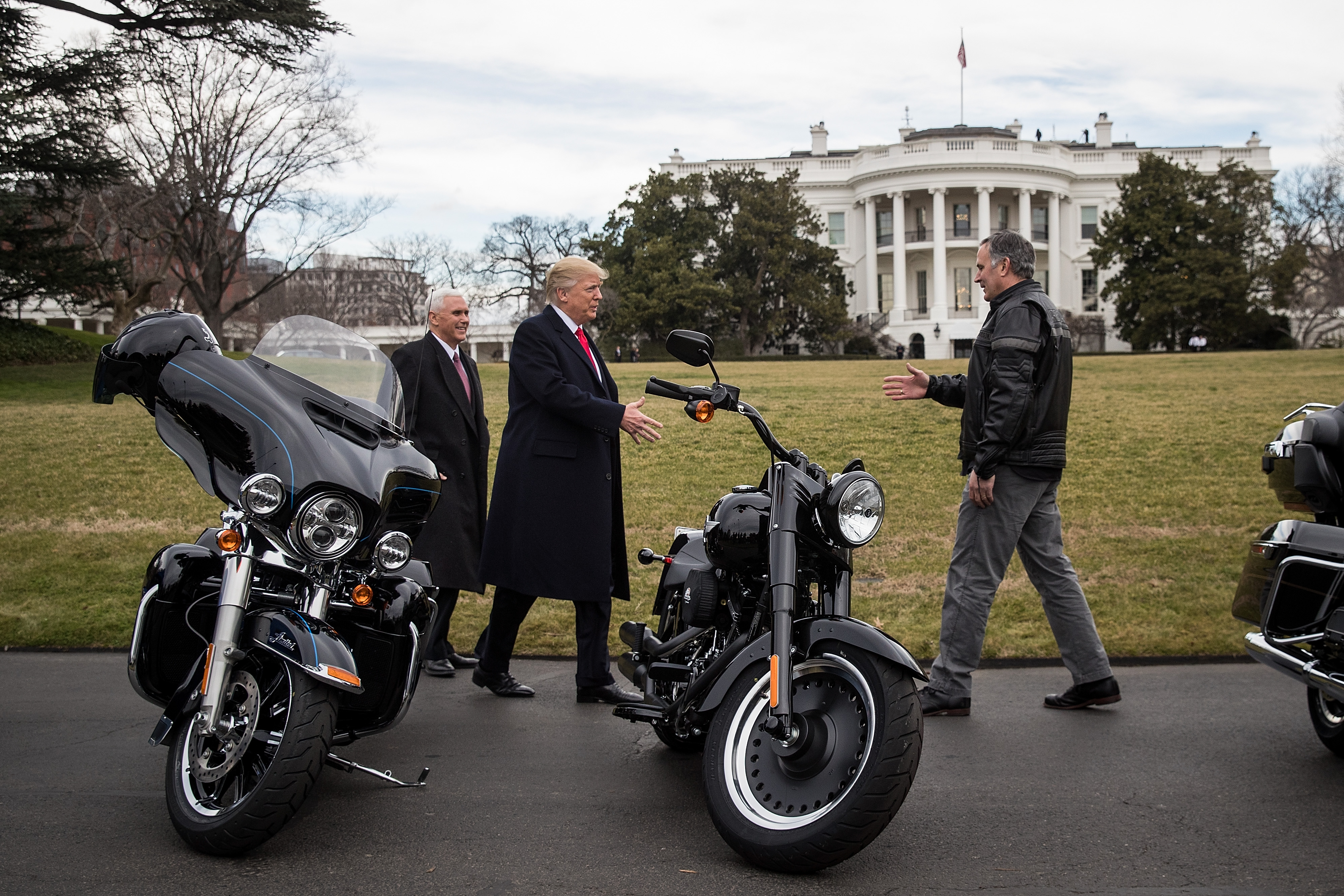 Vice President Mike Pence and President Donald Trump stand beside motorcycles and greet Harley Davidson CEO Matthew Levatich on the South Lawn of the White House, February 2, 2017 in Washington, DC.