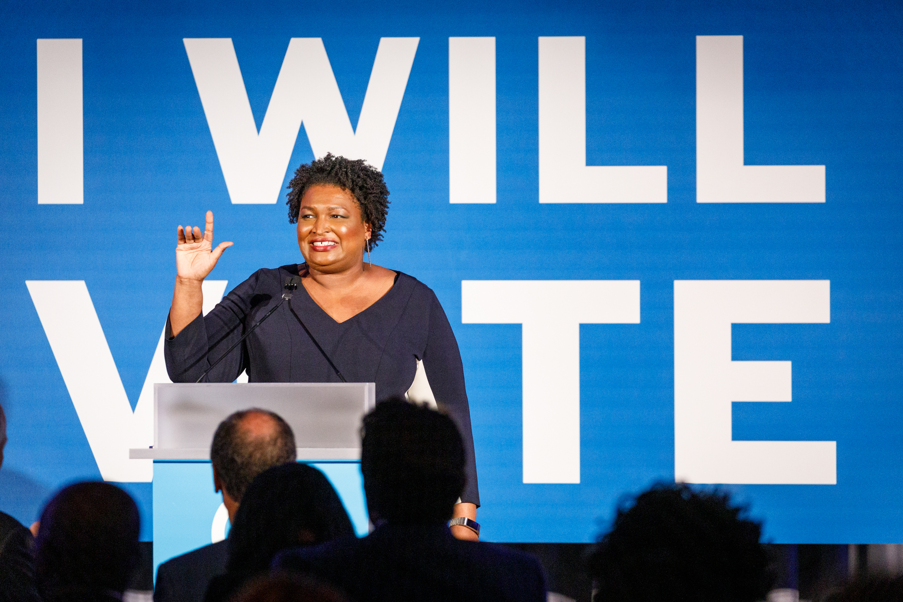 """Stacey Abrams onstage in front of a backdrop that reads, """"I will vote."""""""