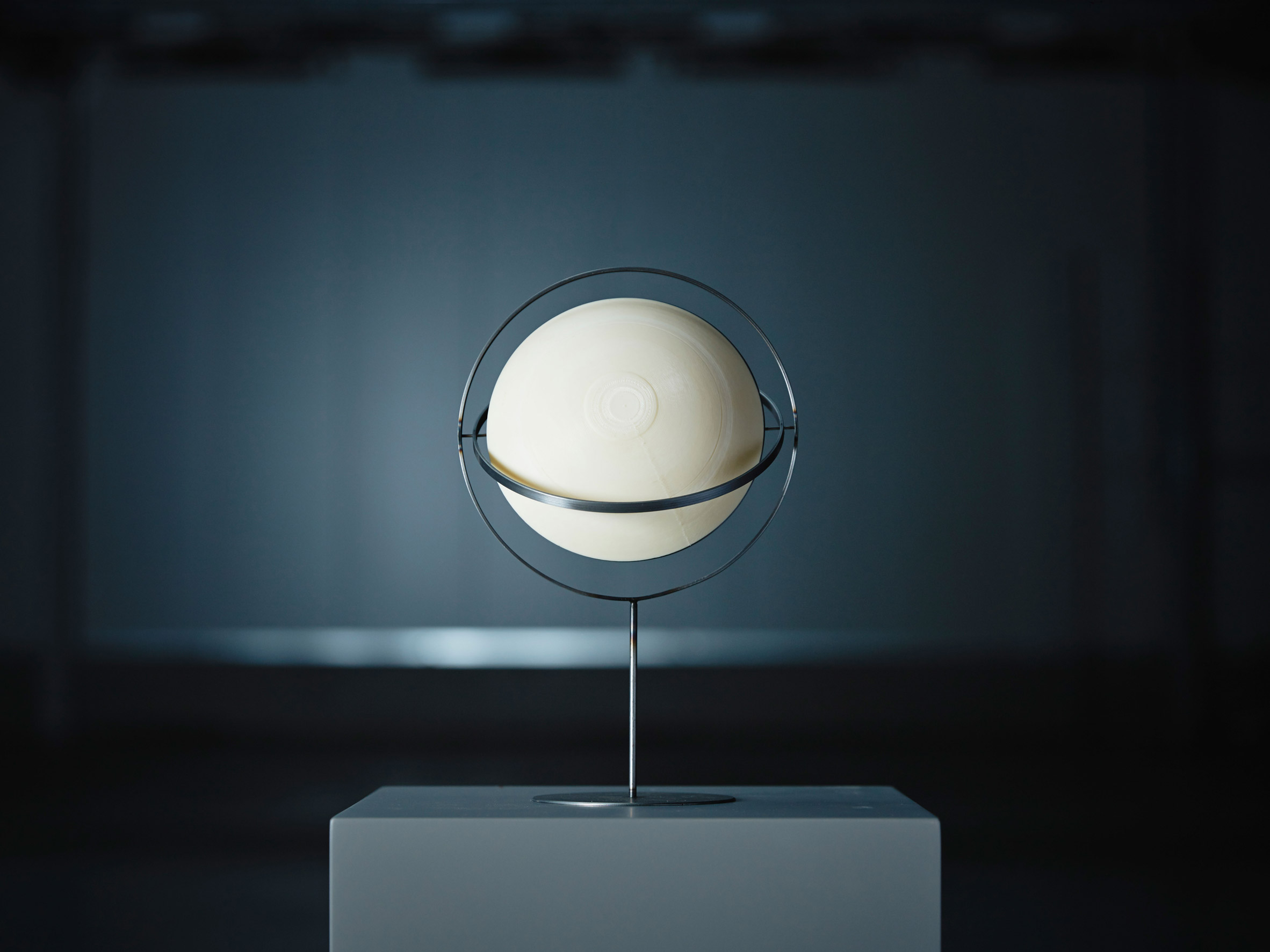 White sphere sitting on metal stand