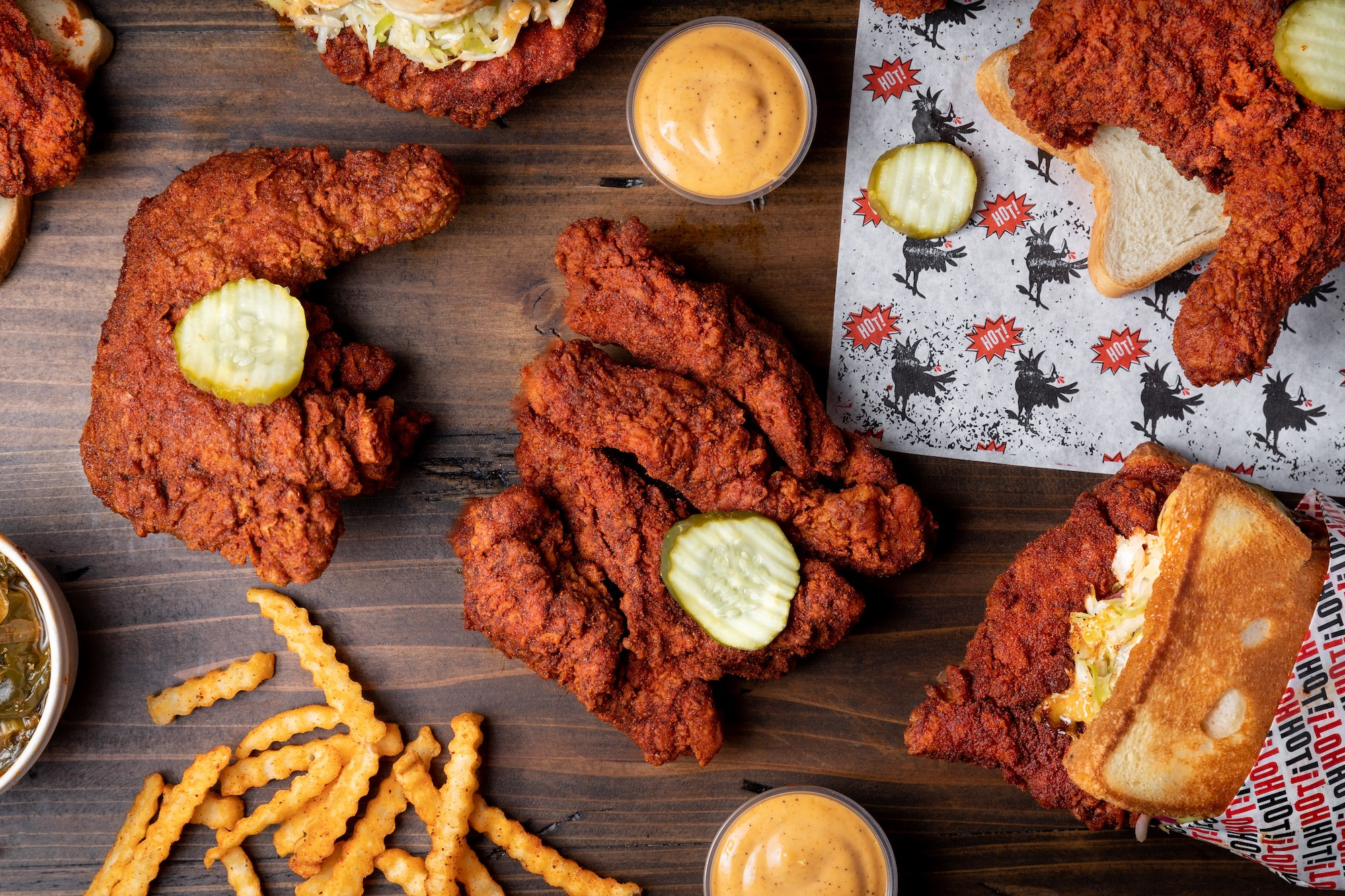 A spread out collection of hot chicken, fries, and sauces from Howlin' Ray's.
