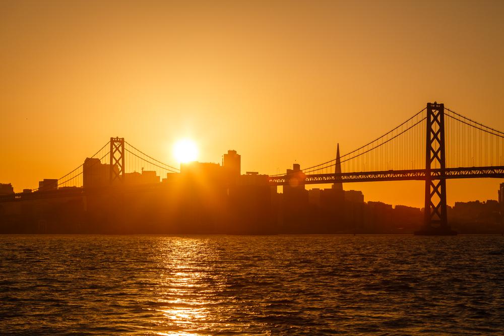 The sun rising in an orange sky over the SF skyline.