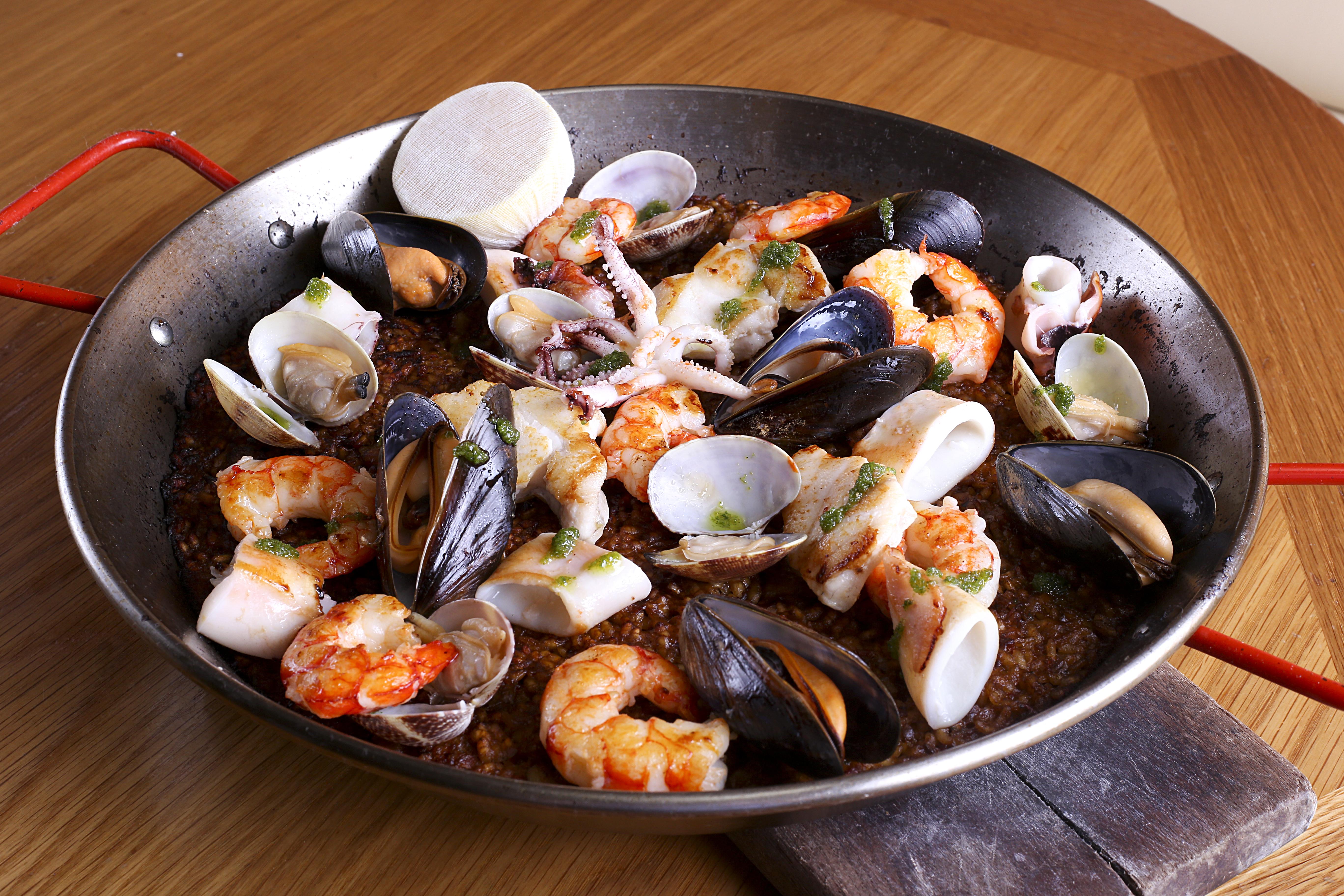Spanish seafood paella in a large metal pan