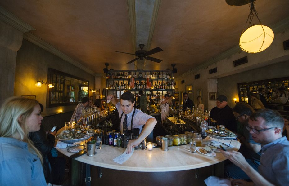 A bartender behind the bar at Maison Premiere