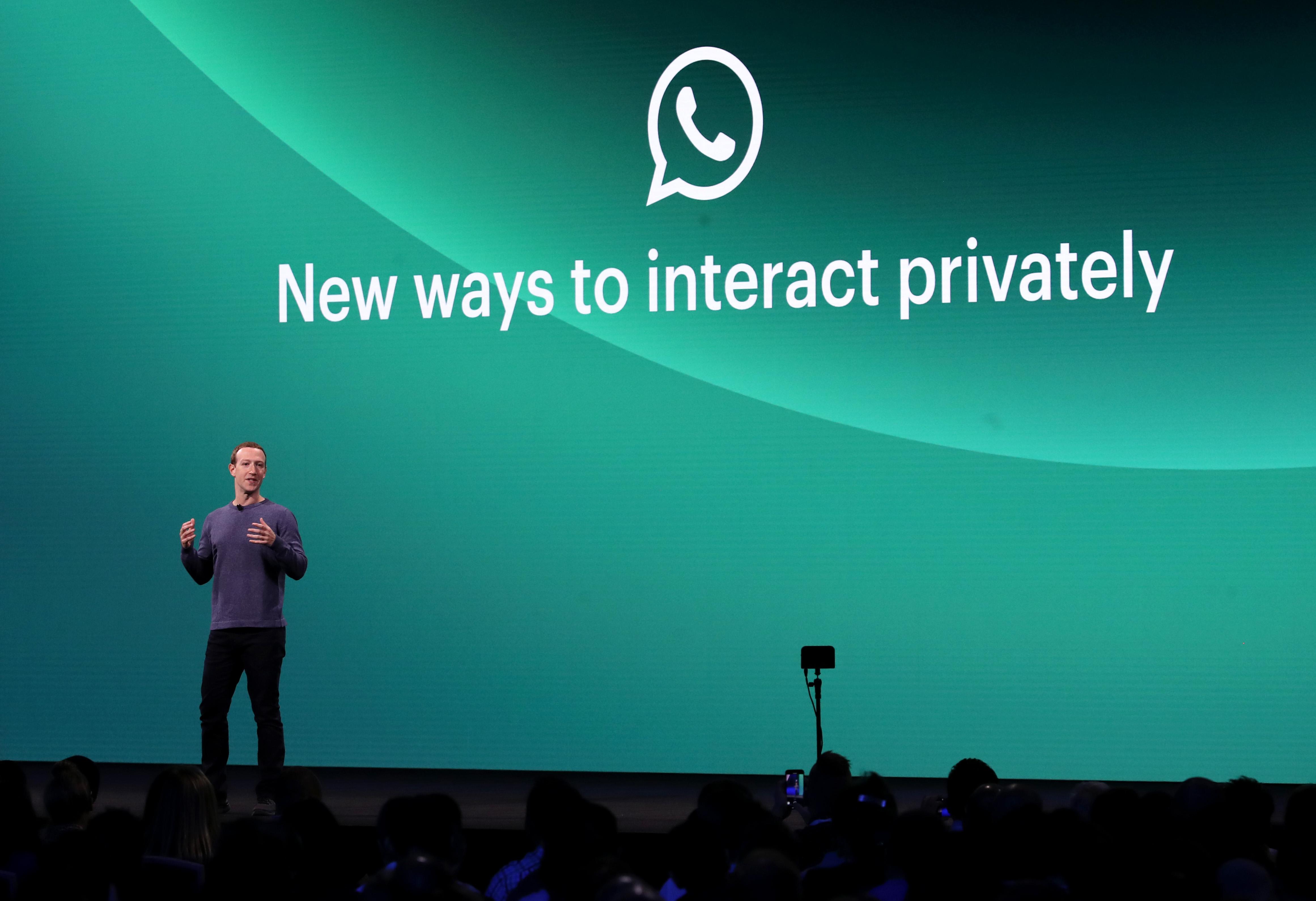 """Facebook CEO Mark Zuckerberg at Facebook's F8 developer conference standing onstage in front of a screen reading, """"New ways to interact privately."""""""