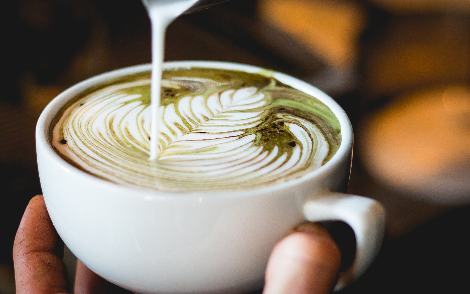 A hand can be seen pouring milk into a large cup to create a leaf like pattern on a latte