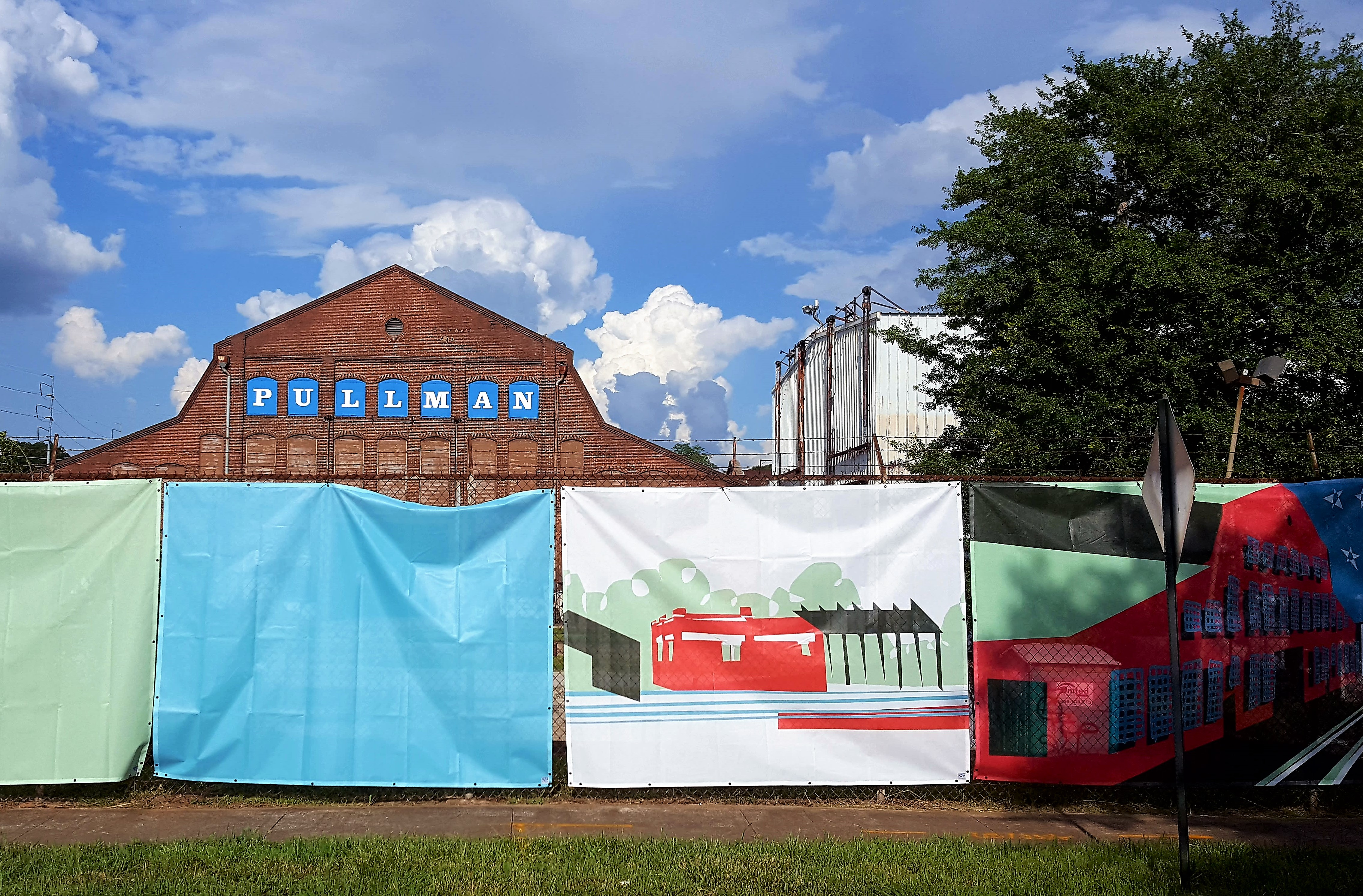 """A colorful construction fence stands before an aging brick building adorned with the word """"Pullman."""""""