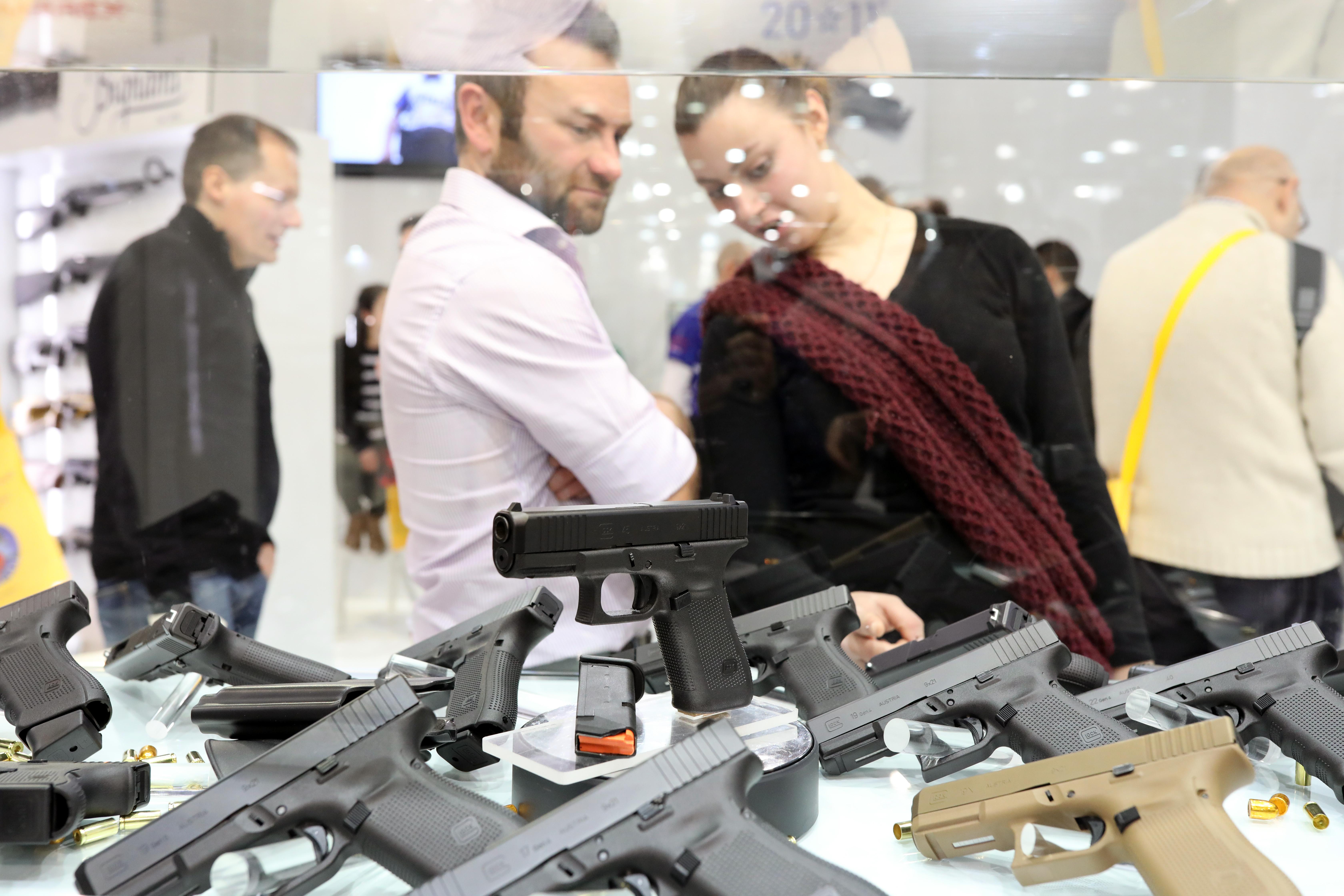 Men looking at guns on display at a trade show.