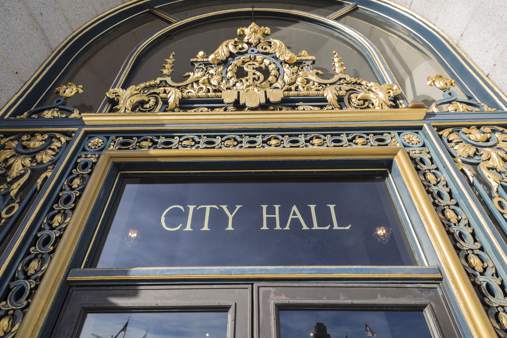 "Gold lettering that says ""City Hall"" above the entrance to the building."