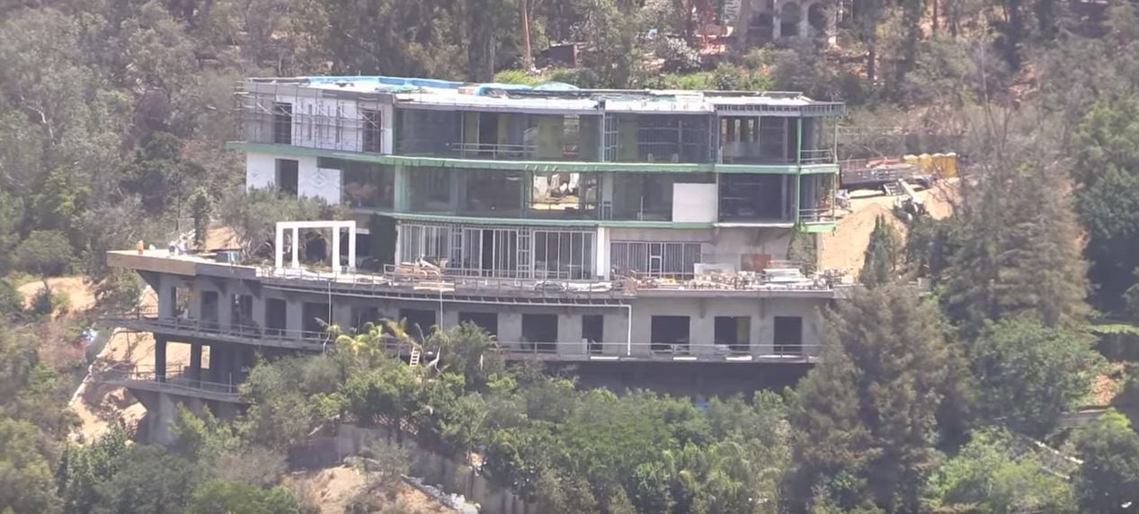 An aerial photo of a half-finished mansion jutting out of a hillside.