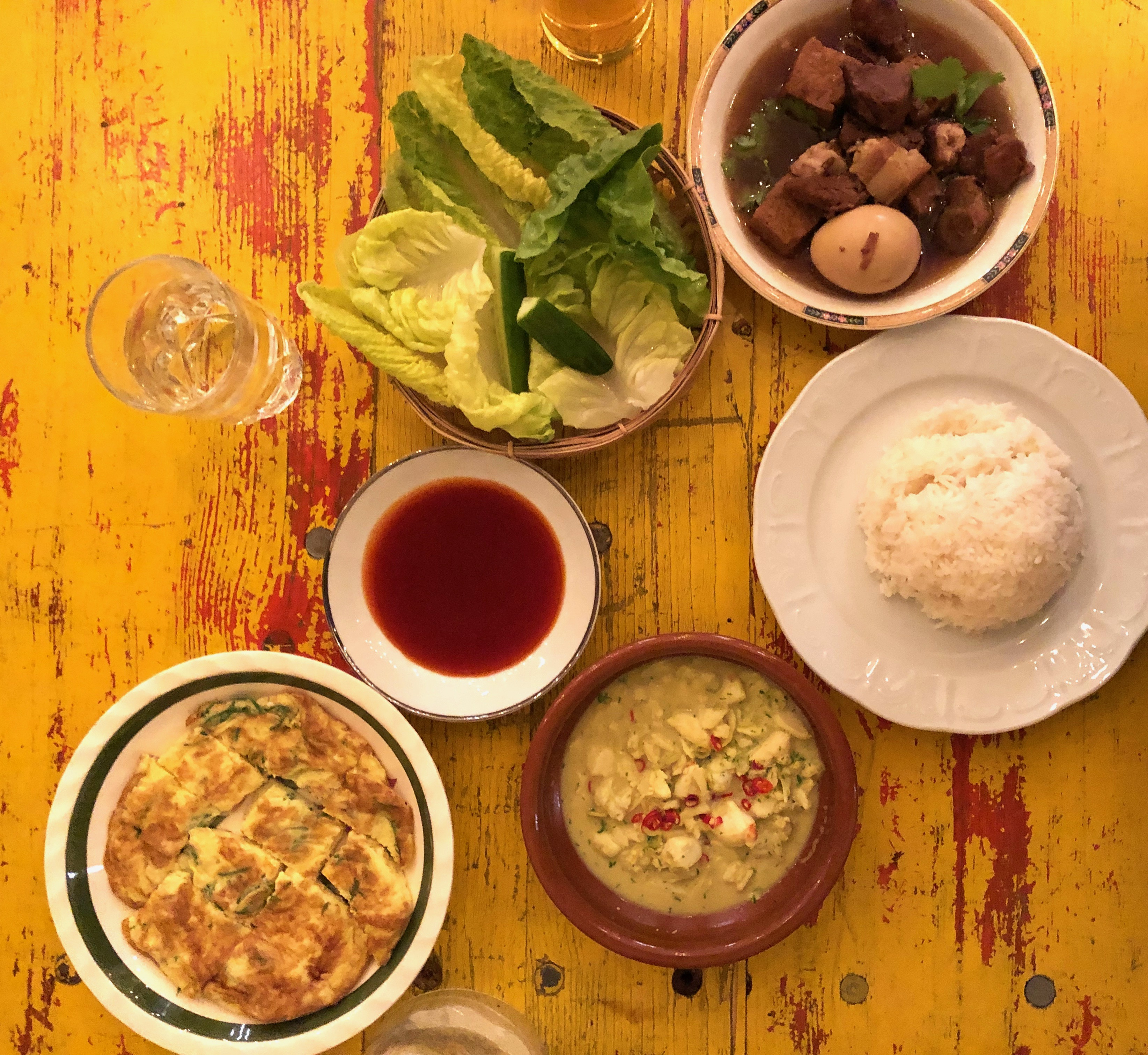 A spread of dishes, including pork belly in a dark soy sauce, green lettuce leaves, a mound of white rice, and a sliced omelet sit over a burnished wood table