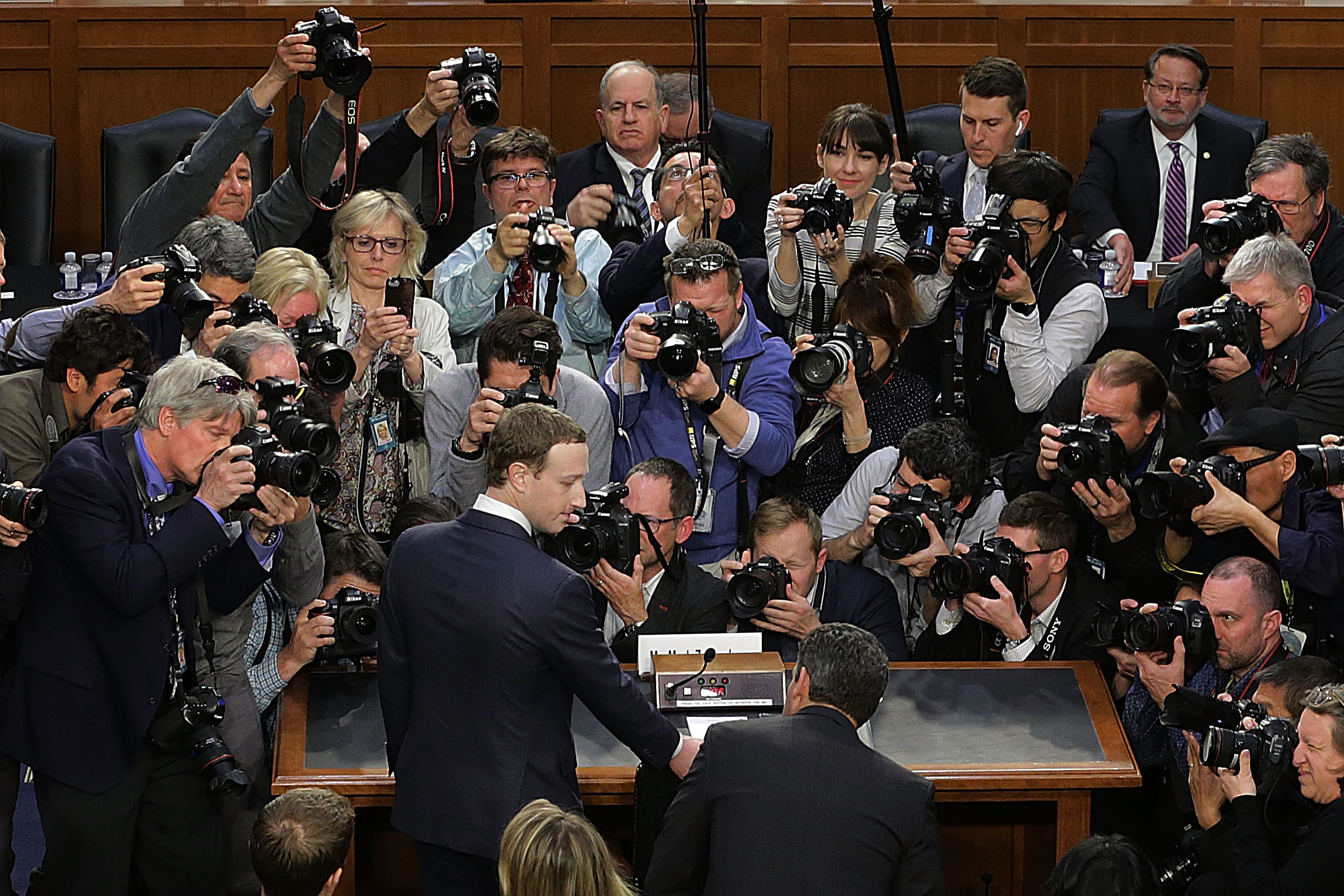 Facebook CEO Mark Zuckerberg surrounded by cameras and microphones and photographers and journalists.